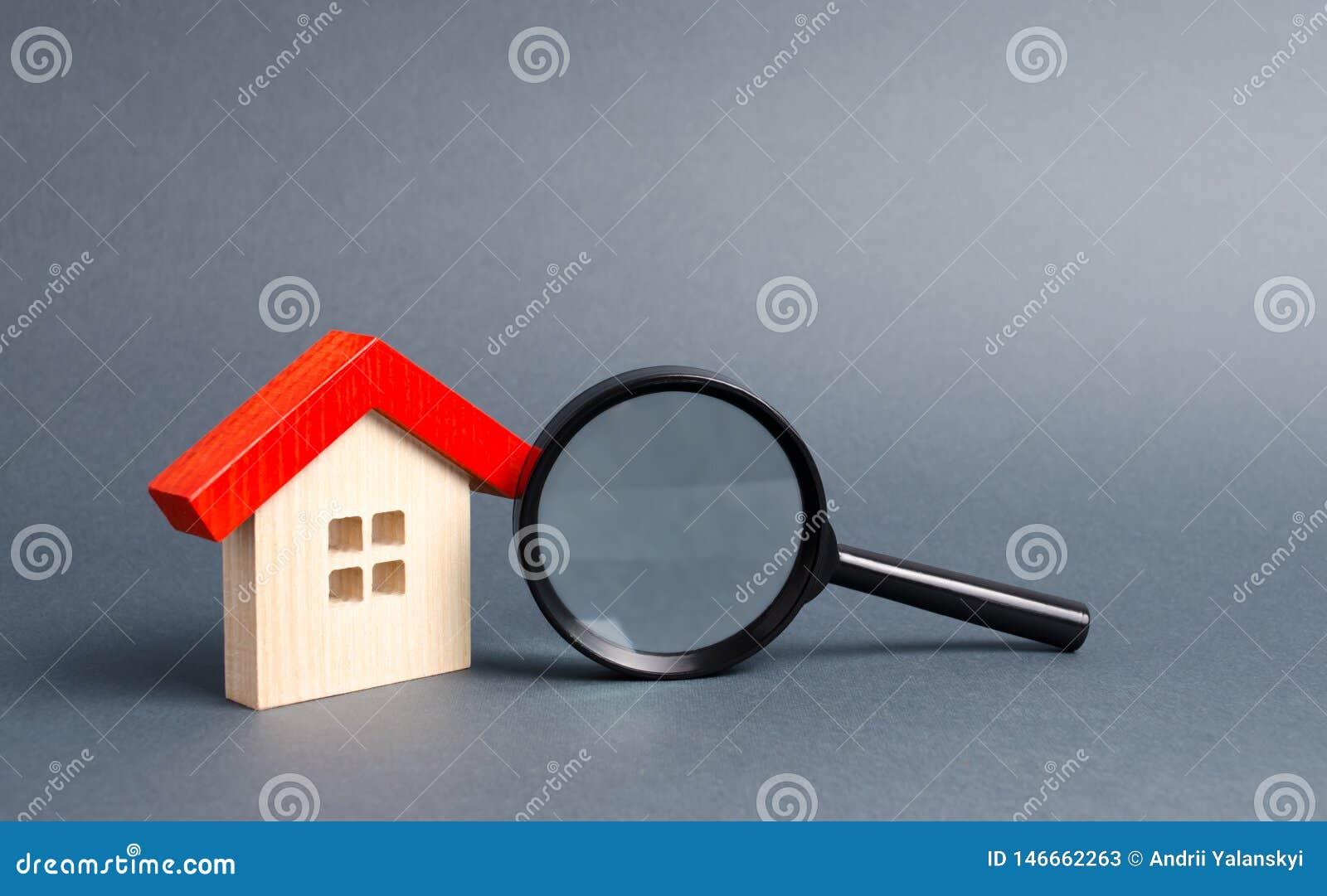 Casa e lente d ingrandimento di legno su un fondo grigio Comprando e vendendo bene immobile, le costruzioni nuove di costruzione,