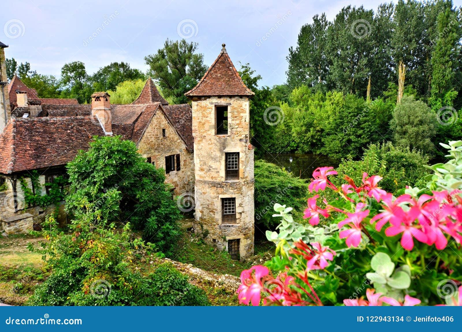 Casa e torre medievais com as flores em Carennac, França