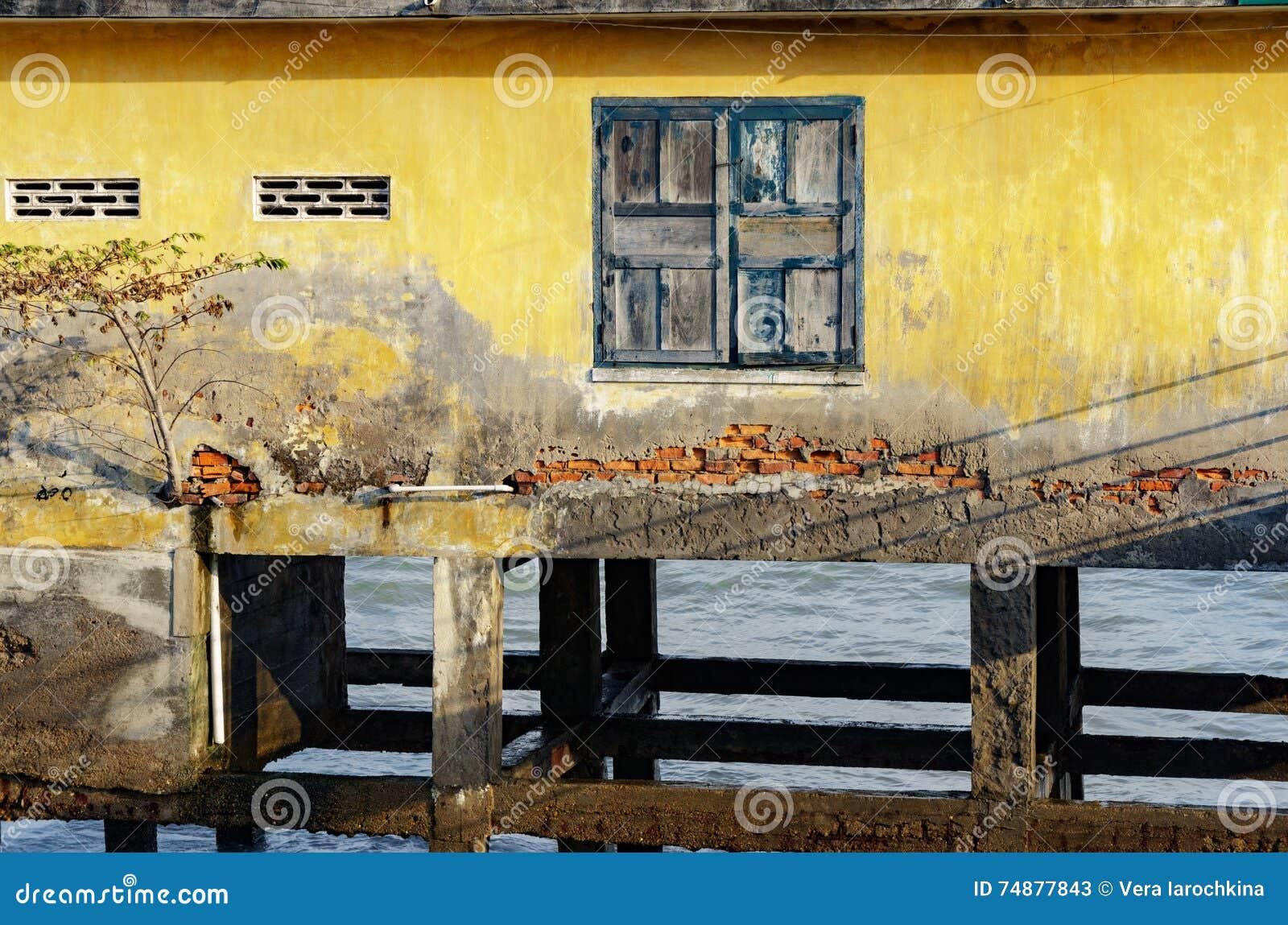 Casa em pernas de pau no mar aberto um quadro de janela com a pintura velha rachada