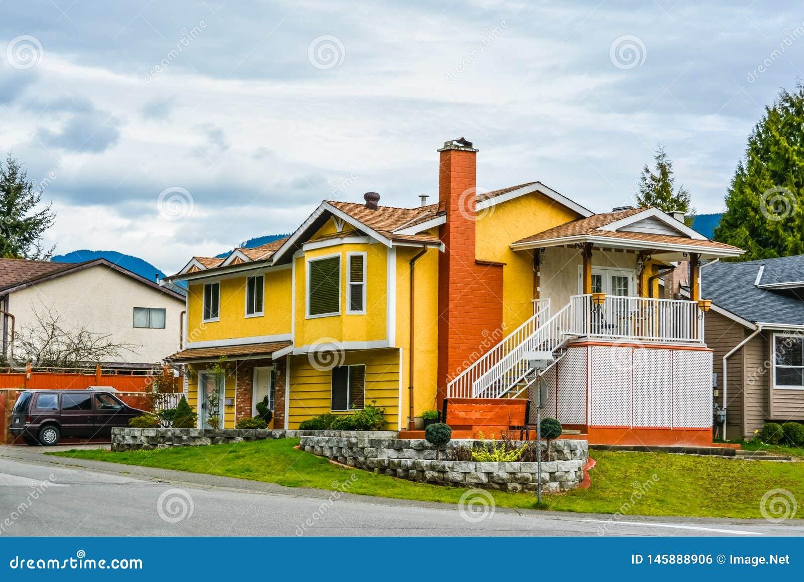 Casa gialla della famiglia con un automobile sulla strada privata sul fondo del cielo nuvoloso