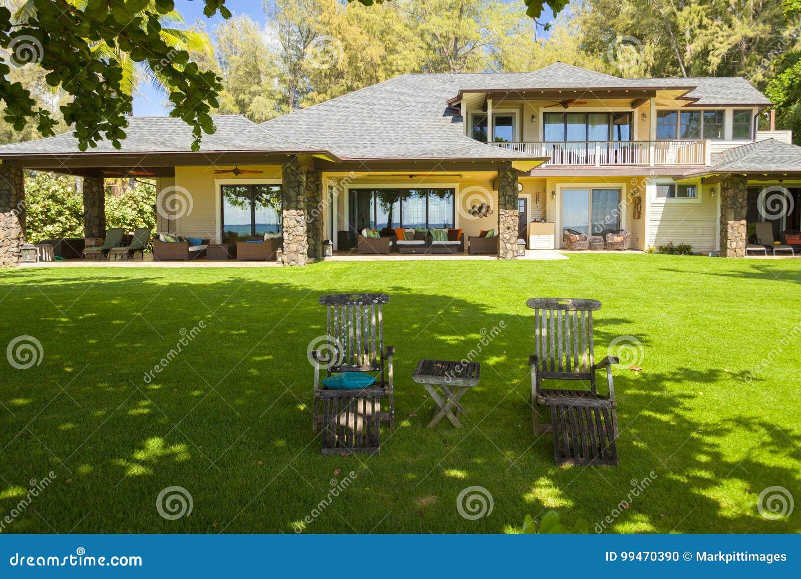 Casa hawaiana grande con la tabla del jardín y sillas en el northshore Oahu Hawaii