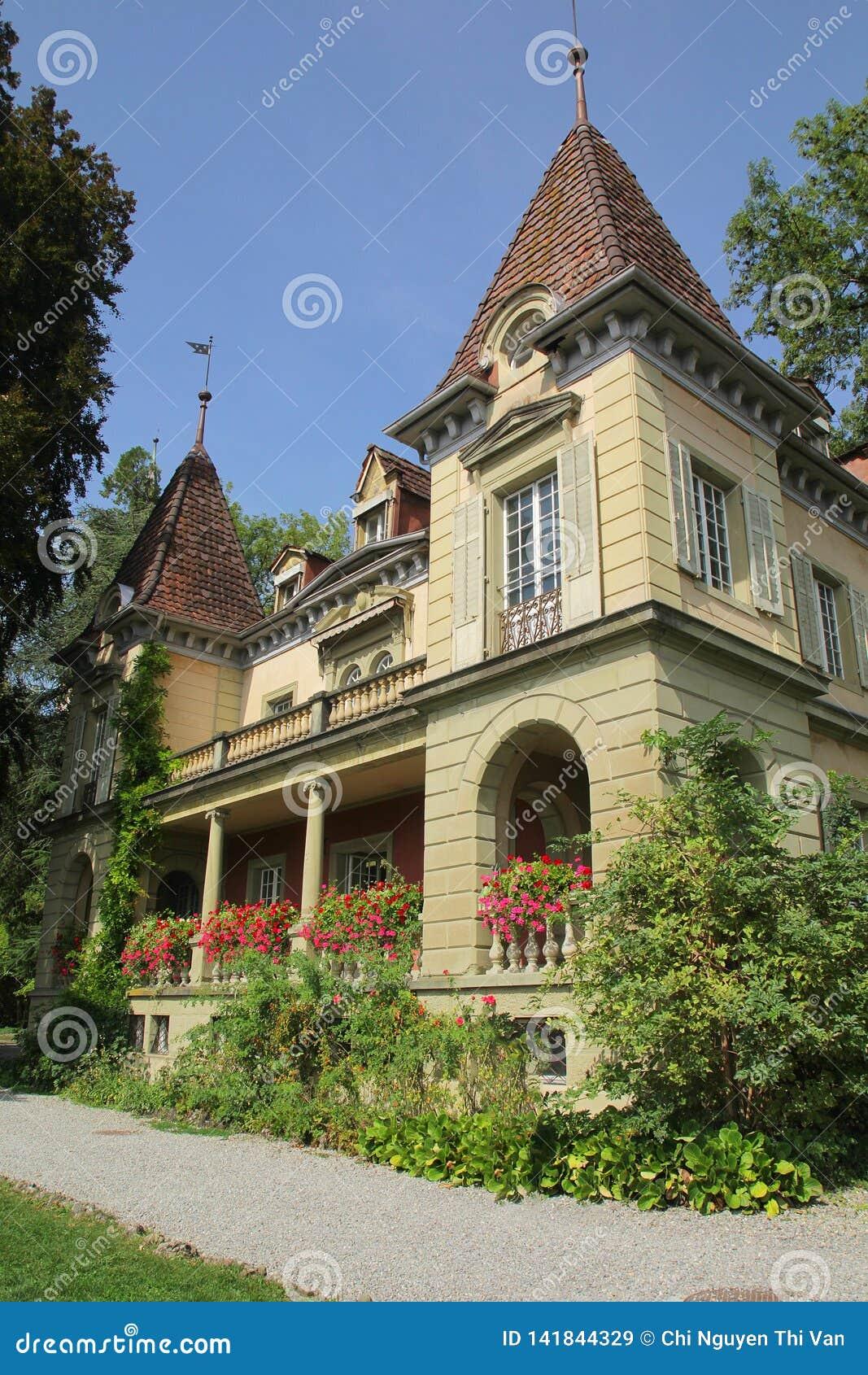 Casa hermosa con las flores en el balcón por la mañana