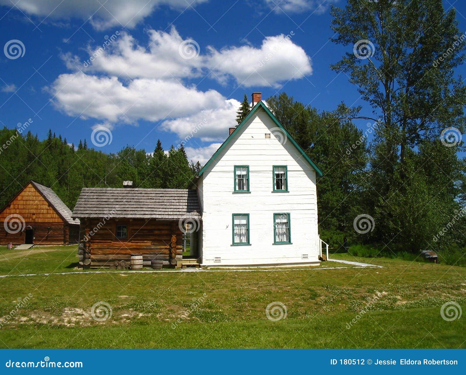 Casa más vieja aserrada blanca de la granja del registro