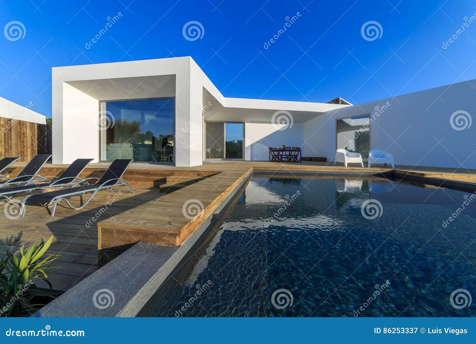 Giardini Moderni Con Piscina : Casa moderna con la piscina del giardino e la piattaforma di legno