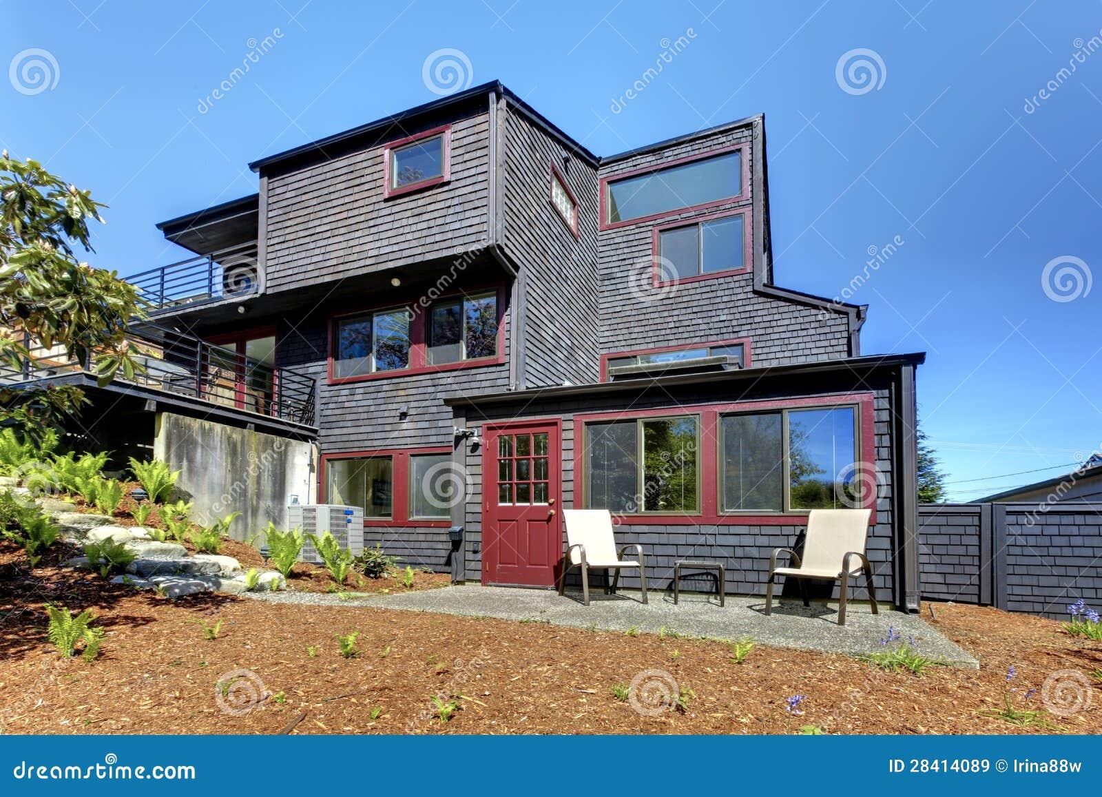 casa moderna di legno nera con il cortile della sorgente