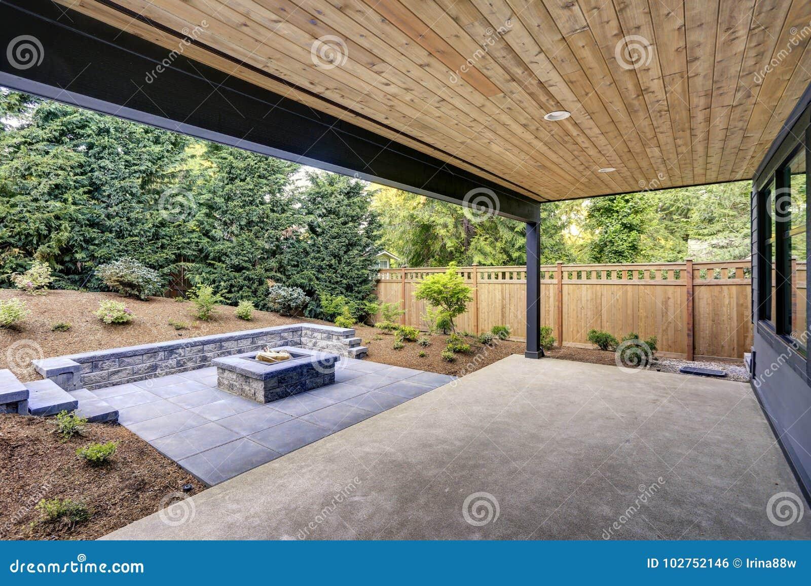 A casa moderna nova caracteriza um quintal com pátio
