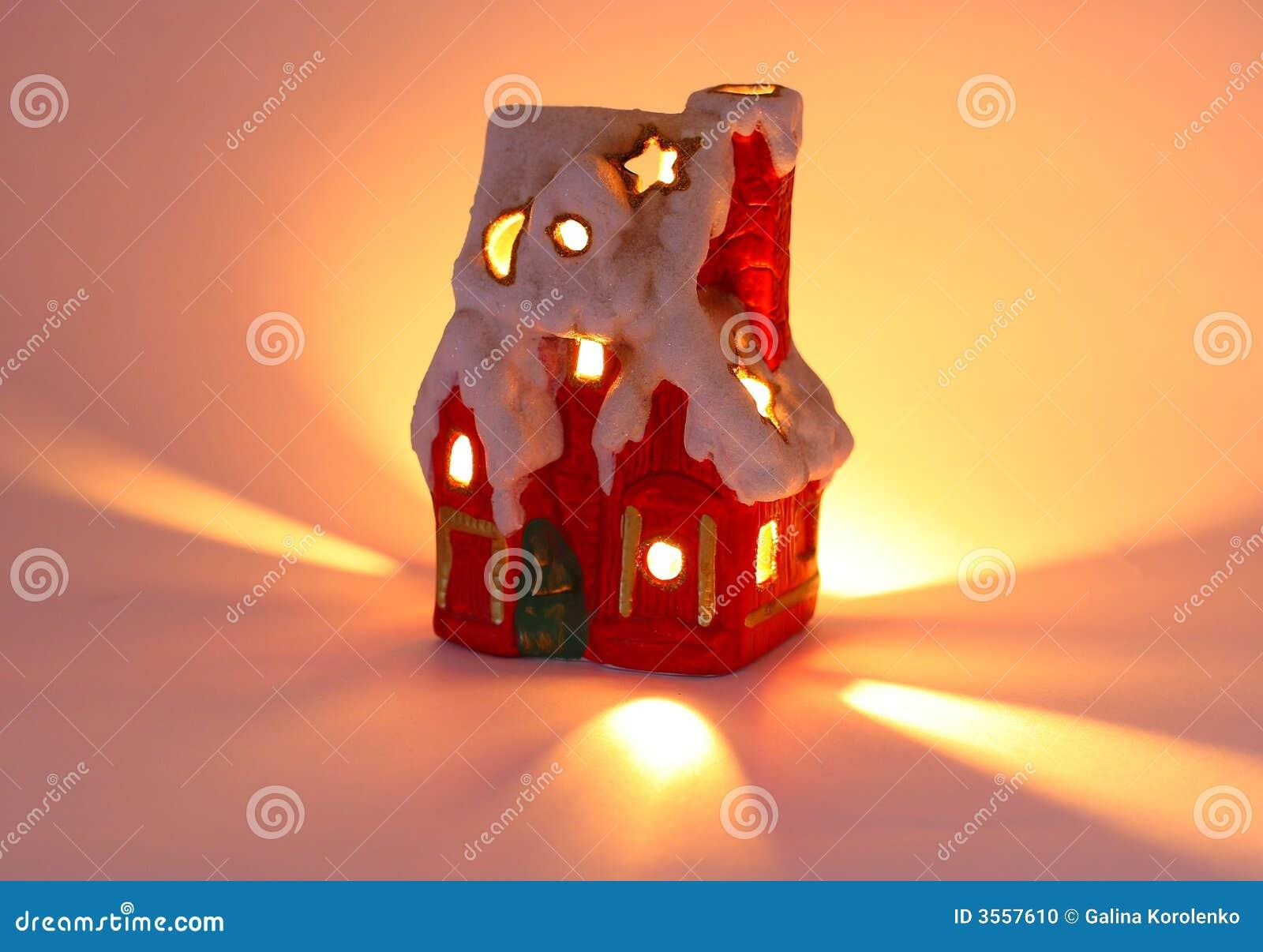 Casa molto piccola e candela di natale di colore rosso