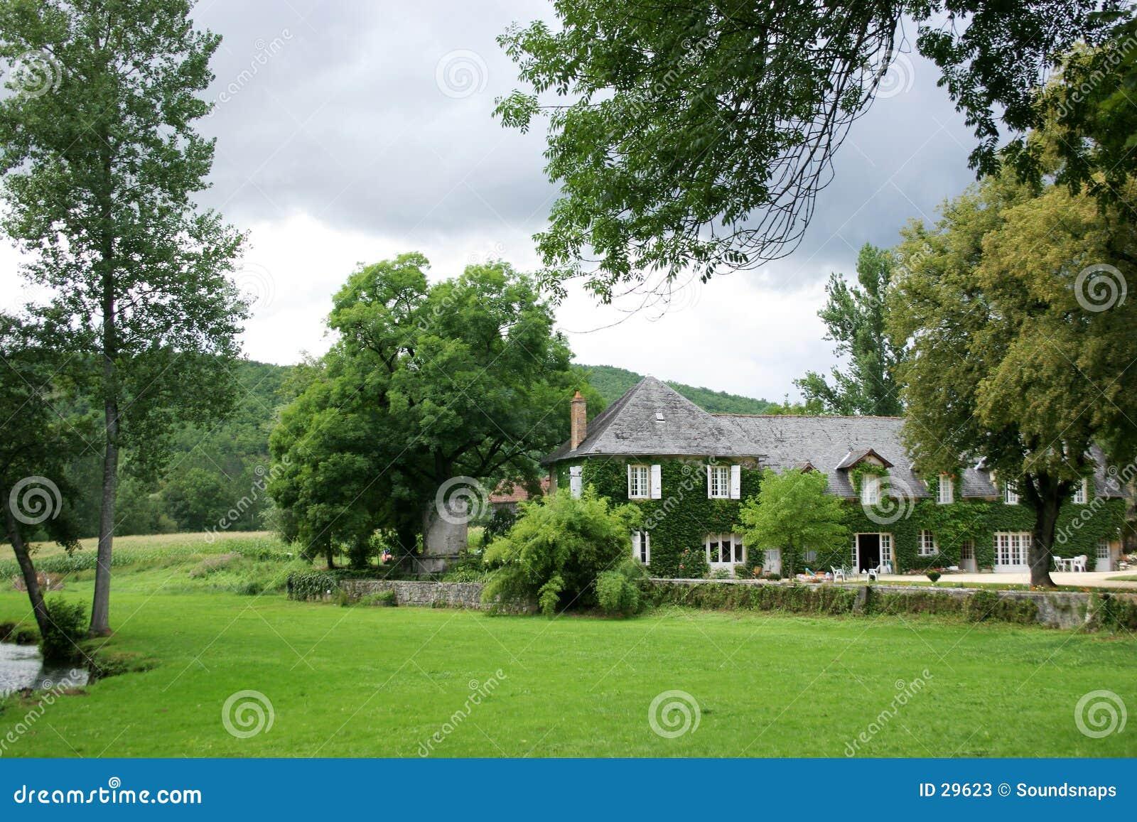 Casa no jardim do país atrás das árvores