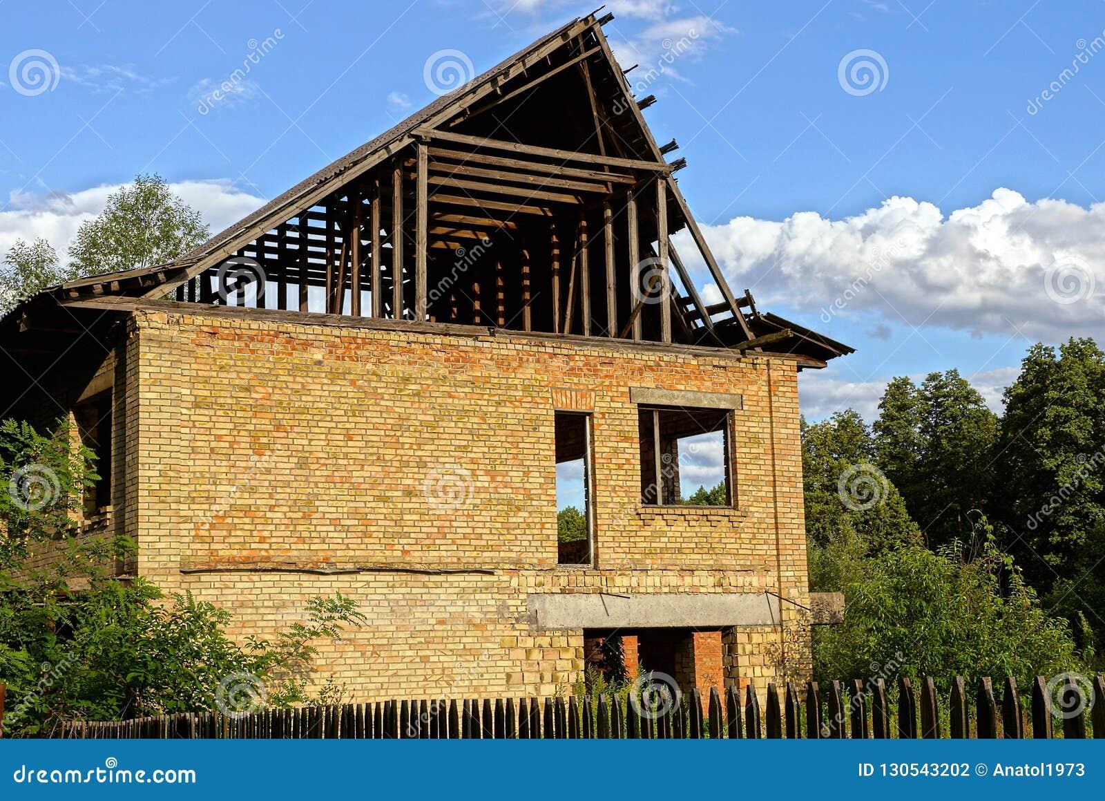 Casa non finita del mattone marrone e del tetto di legno fra gli alberi verdi dietro il recinto