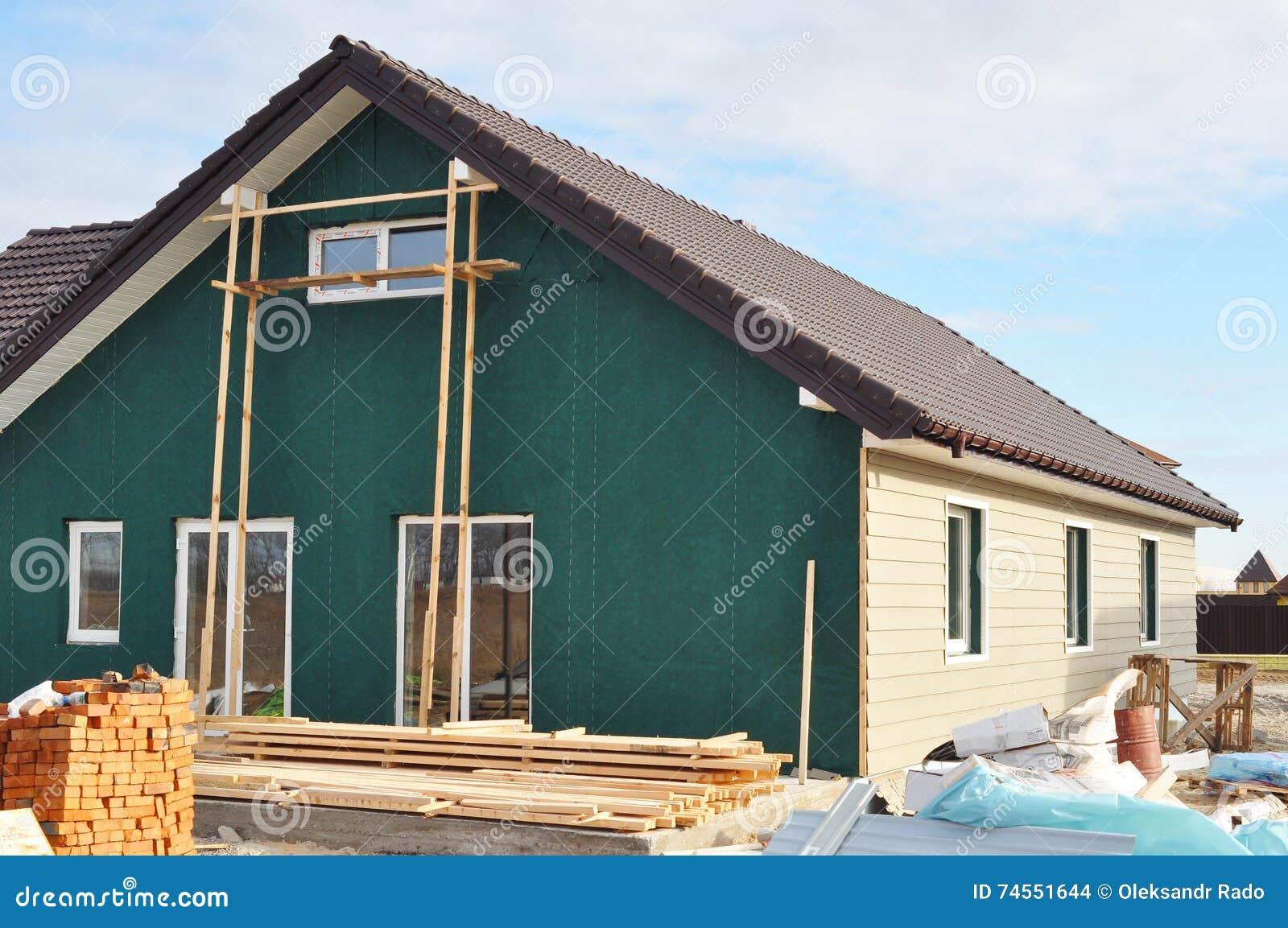 Casa nova de construção com a membrana plástica do tapume e da isolação na parede exterior da casa