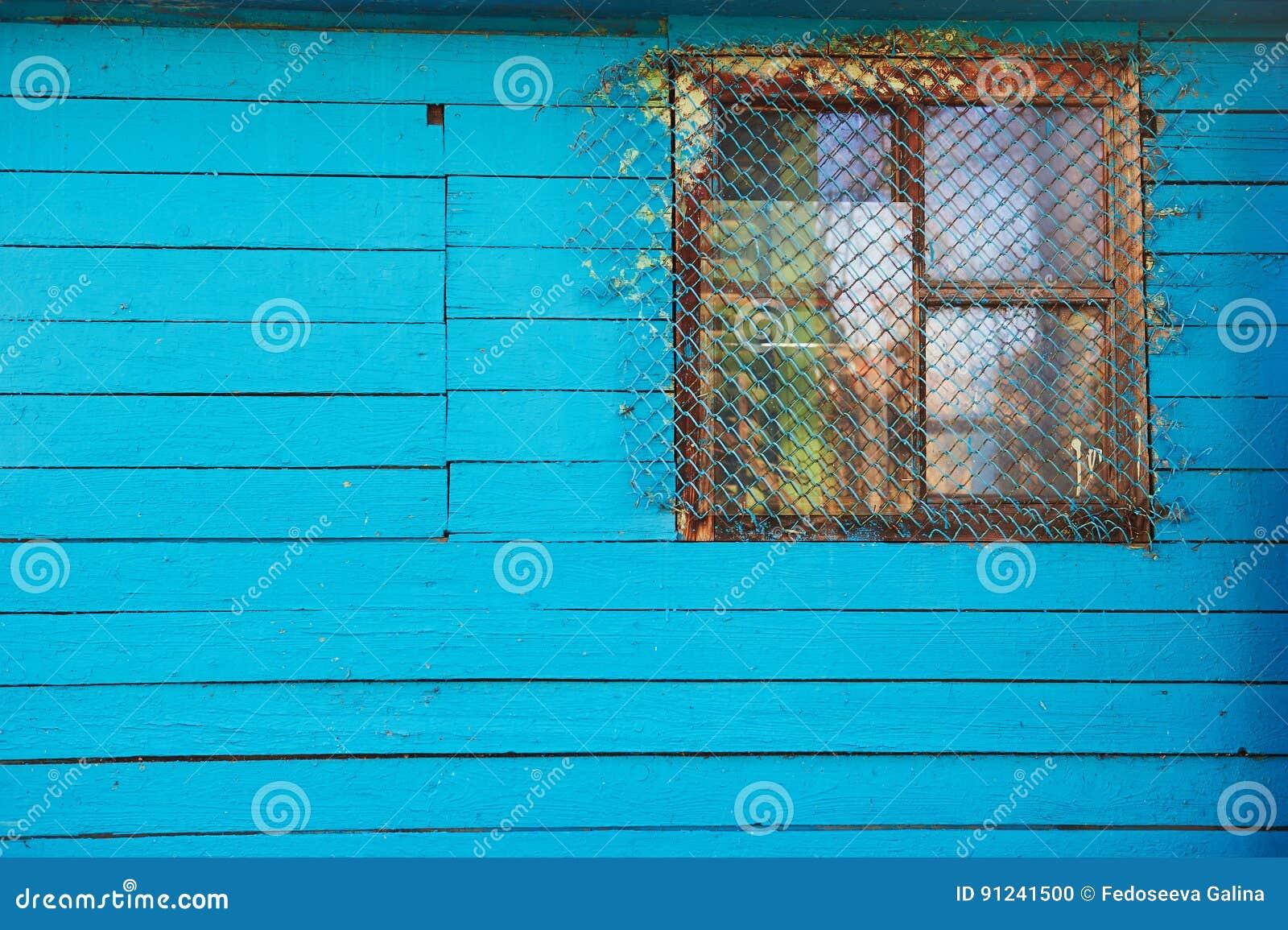 Casa o granero azul de madera vieja con una pequeña ventana barrada