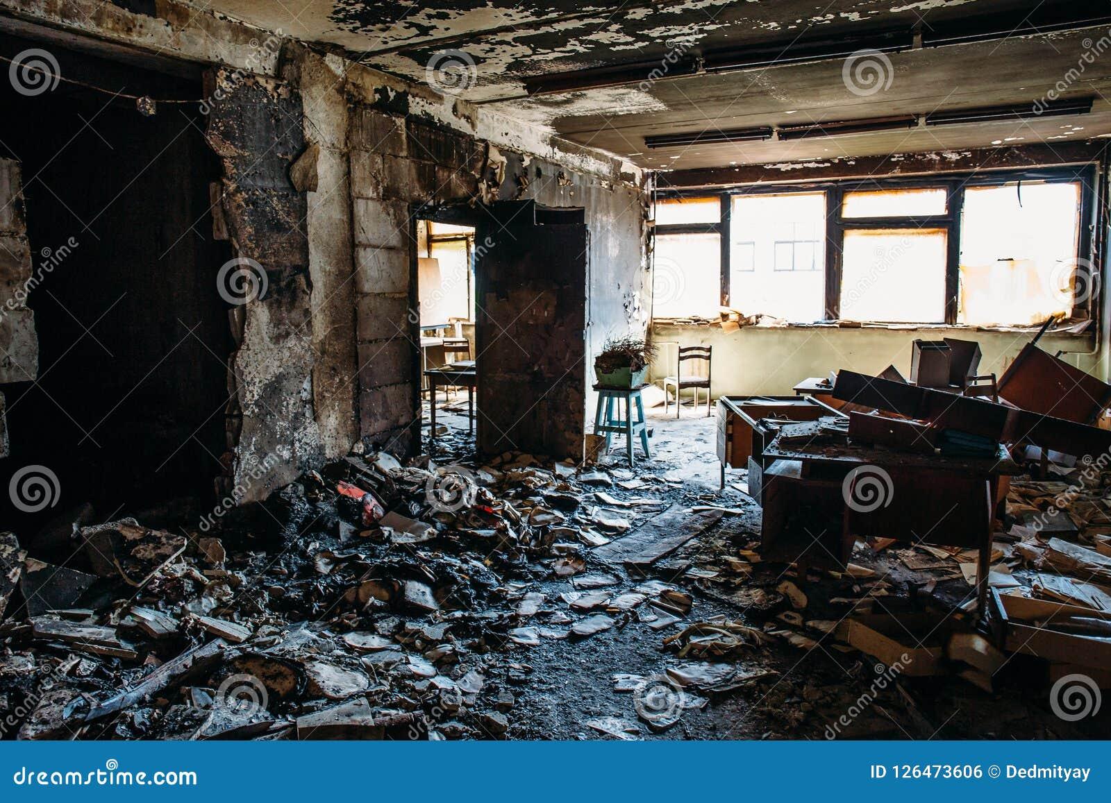 Casa queimada interior Sala queimada na construção industrial, na mobília carbonizada e no apartamento danificado após o fogo
