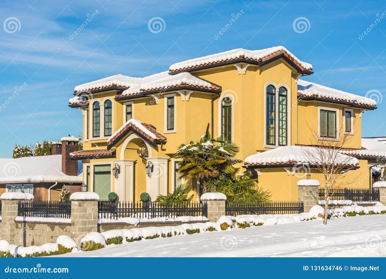 Casa residencial luxuoso na neve no dia ensolarado do inverno em Canadá