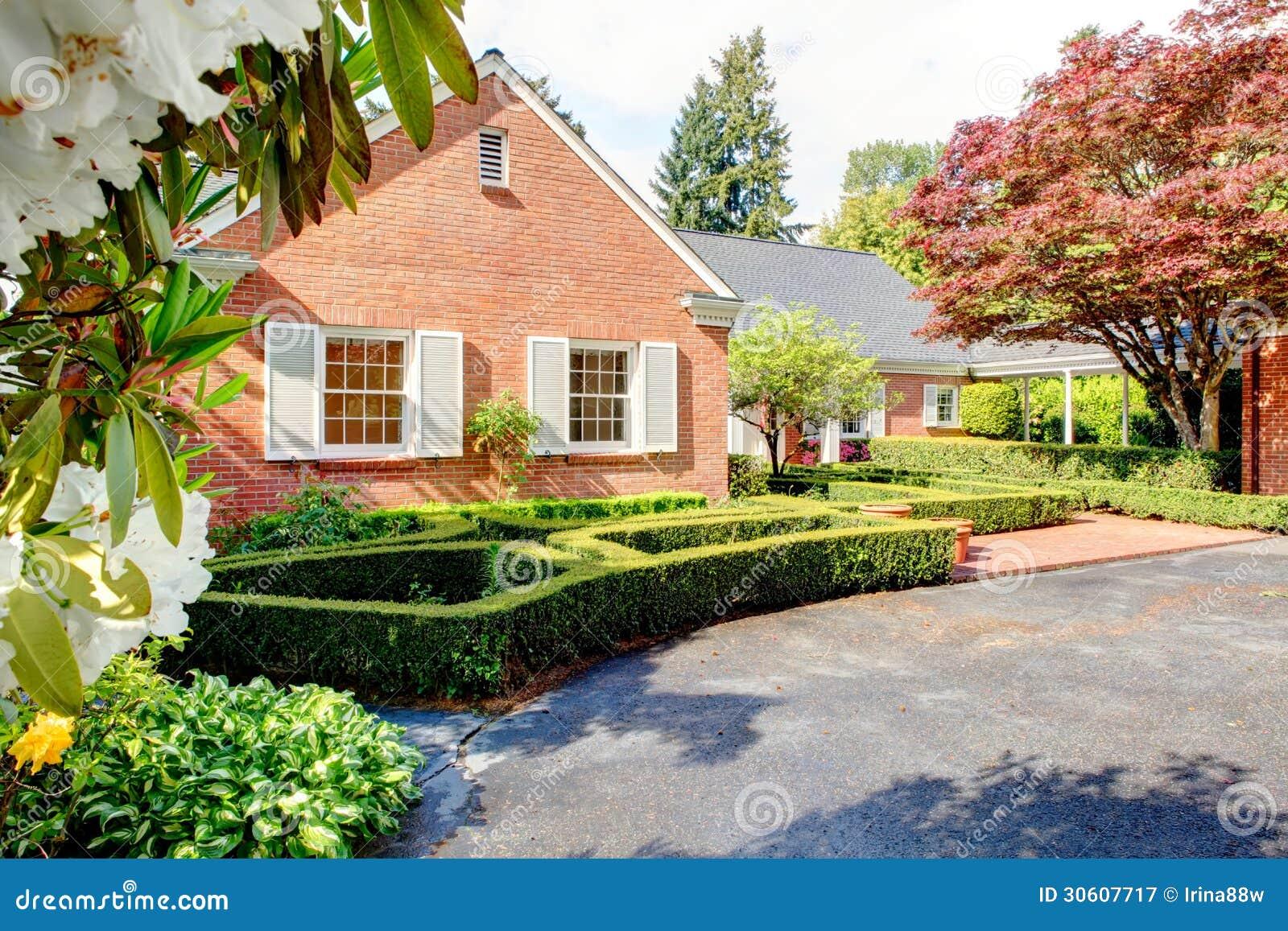 Casa rossa mattone con il giardino inglese e gli for Casa giardino