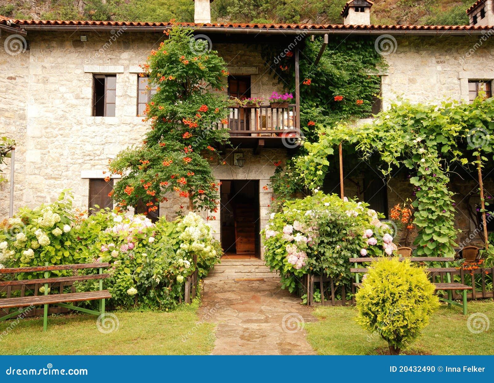 Casa rurale variopinta con il giardino fotografia stock for Casa di costruzione in metallo con avvolgente portico
