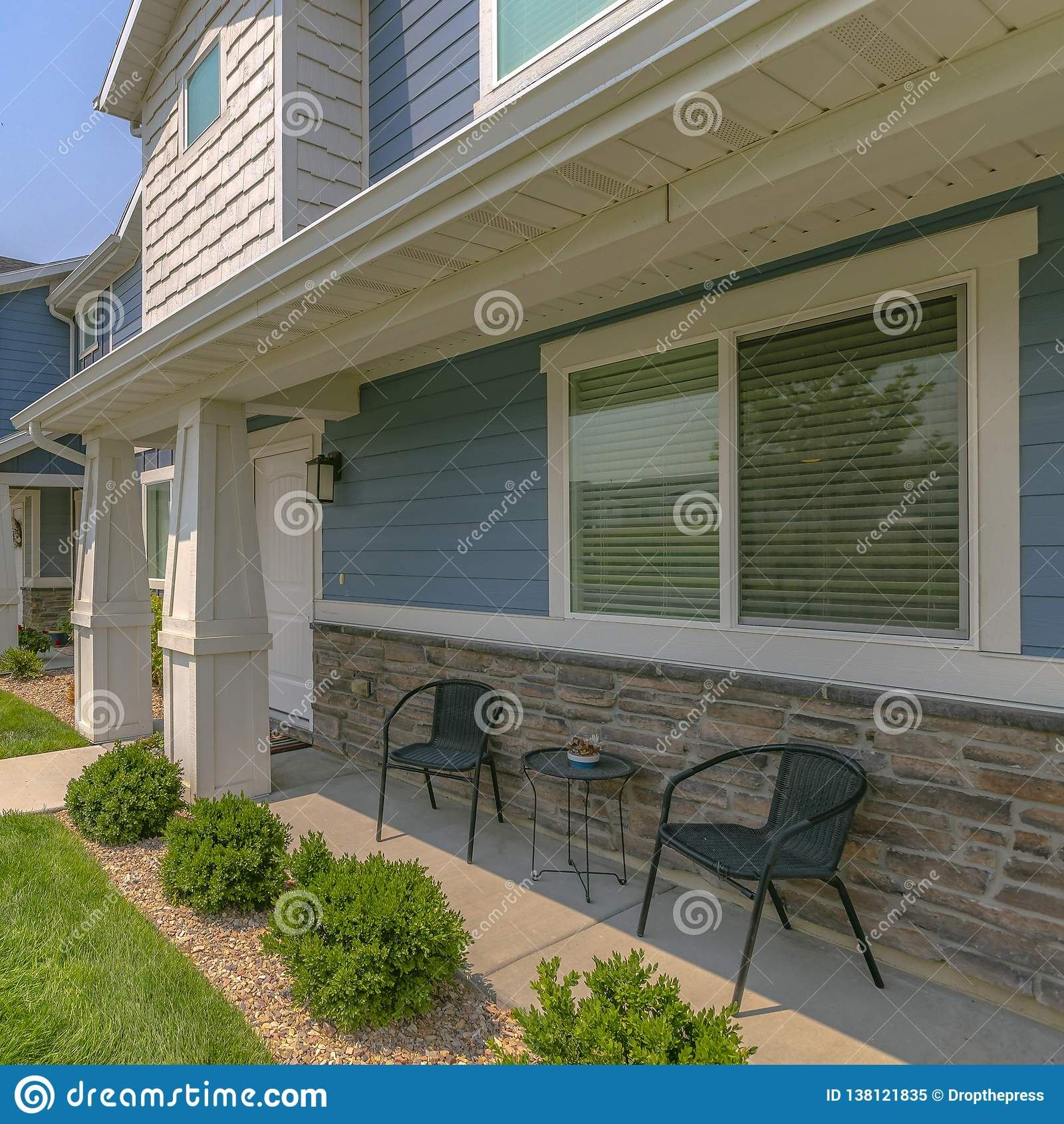 Casa soleggiata con le mobilie sul piccolo portico