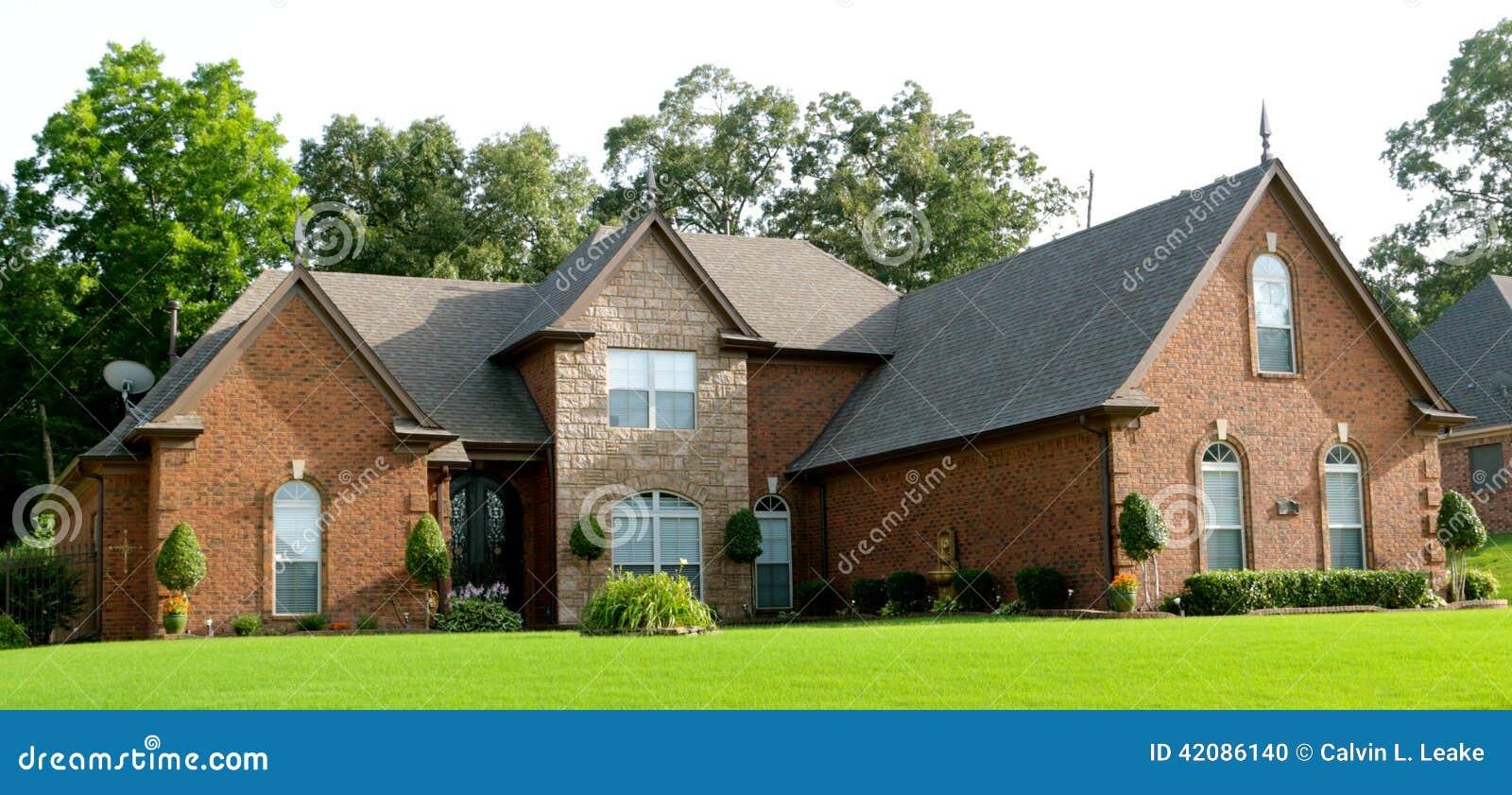 Casa suburbana bonita com gramado verde luxúria