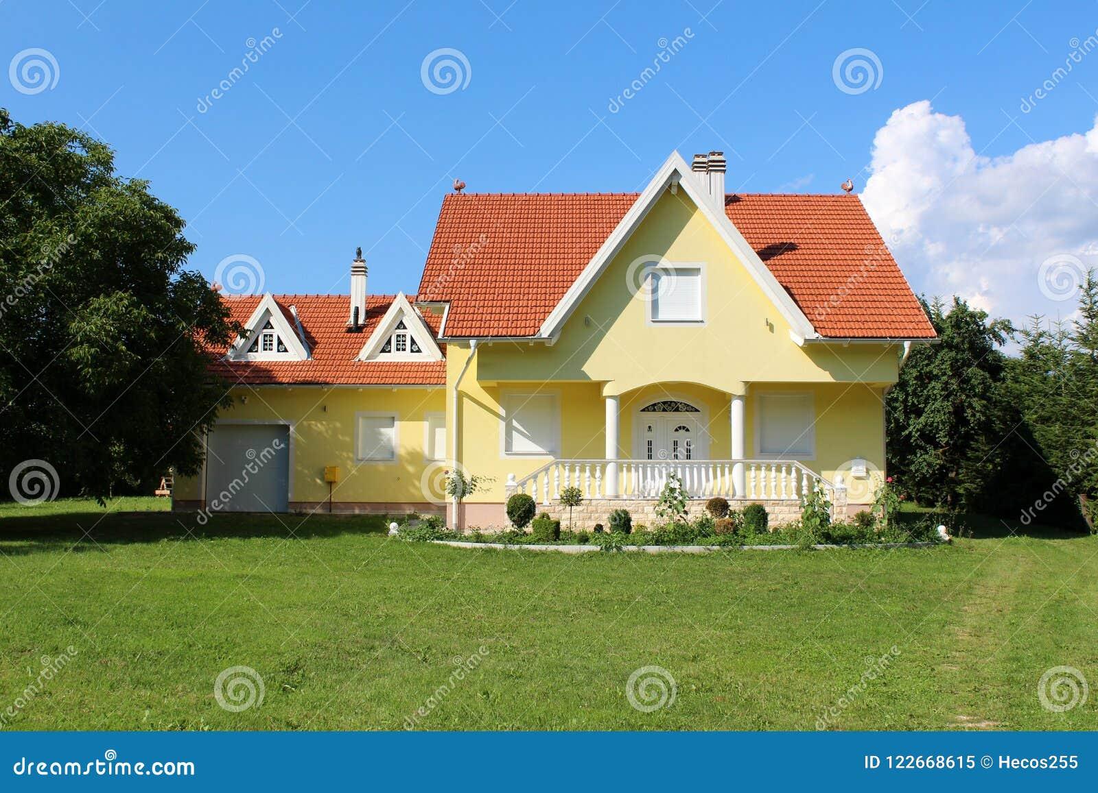 Casa suburbana gialla moderna della famiglia con il piccolo garage accanto