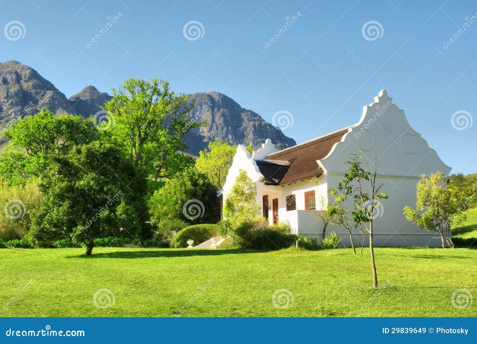 Casa holandesa do cabo tradicional contra montanhas