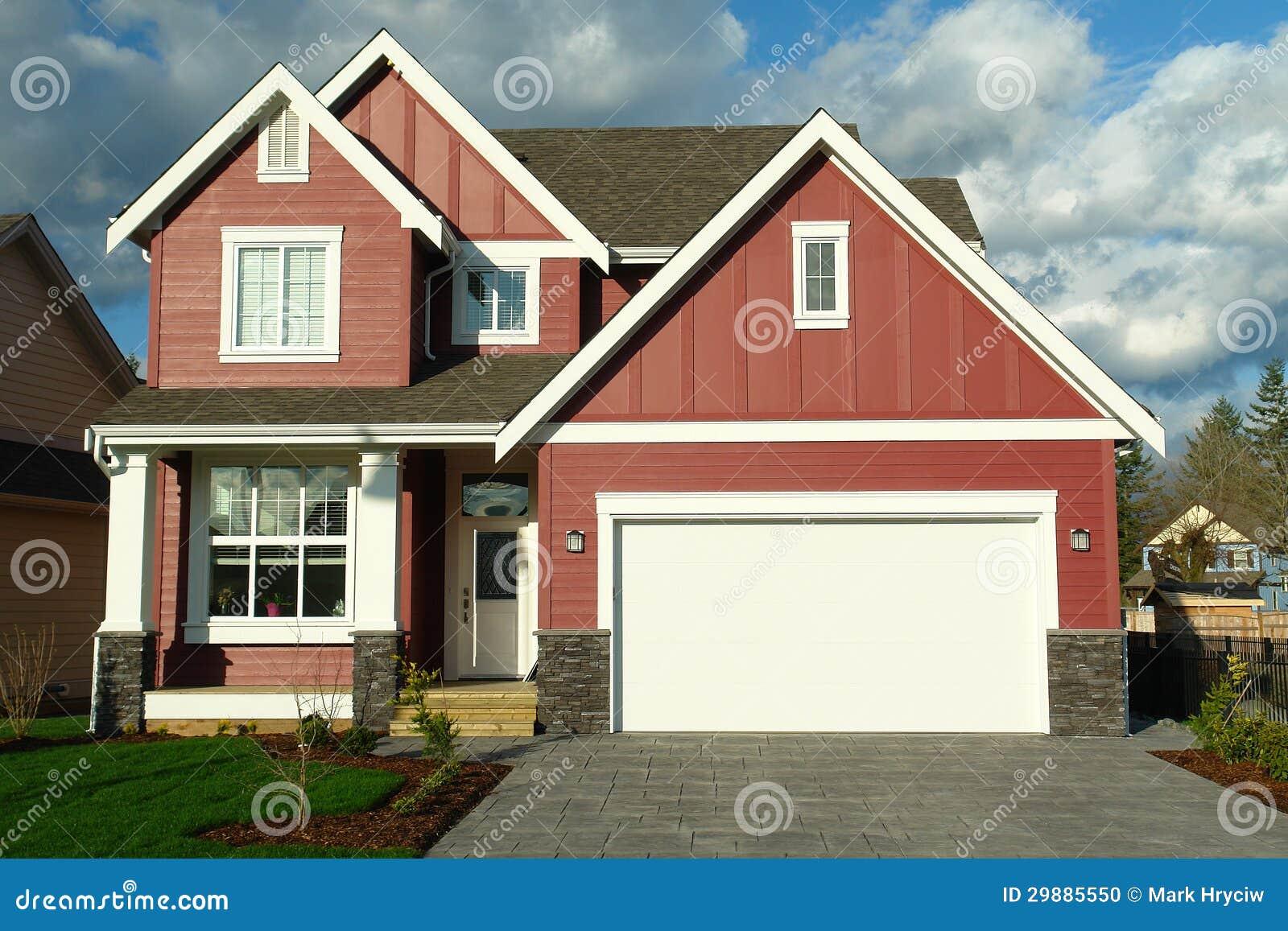Casa vermelha nova da casa com guarnição branca