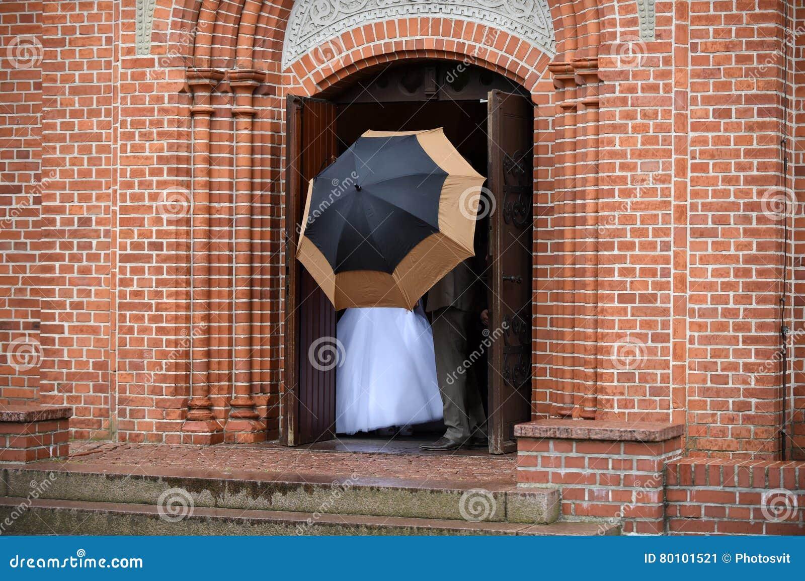Casal atrás do guarda-chuva