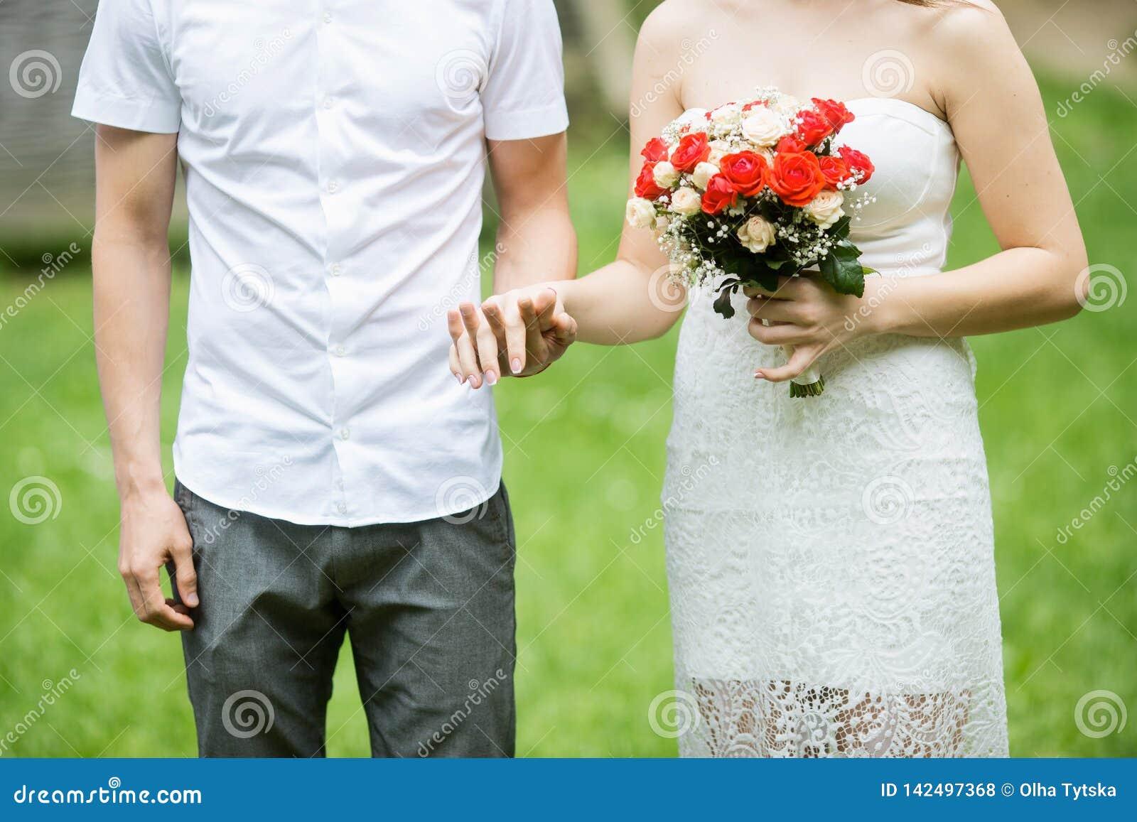 Casal feliz que mantém as mãos exteriores com flores