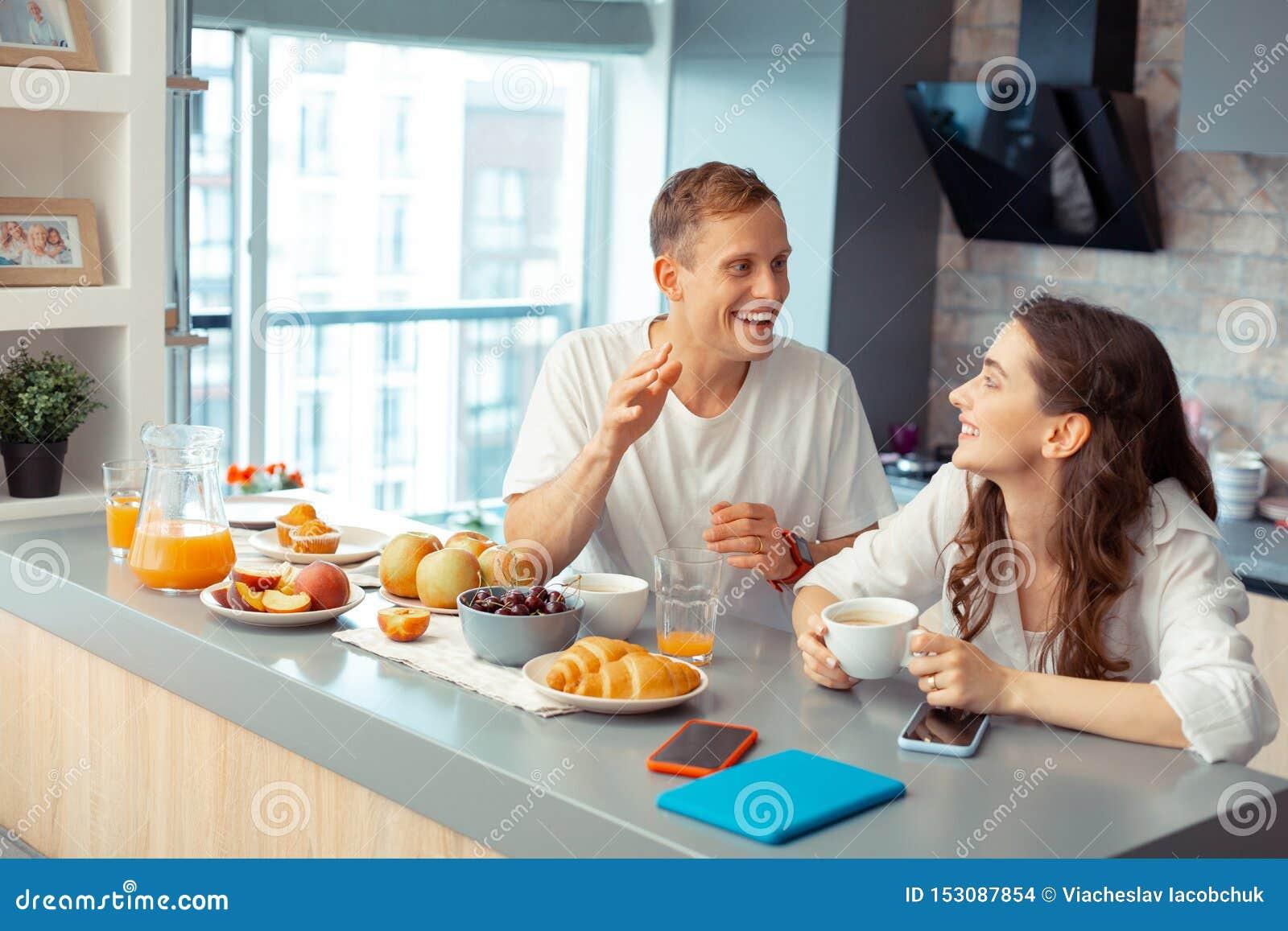 Casal justo feliz que aprecia o café da manhã junto