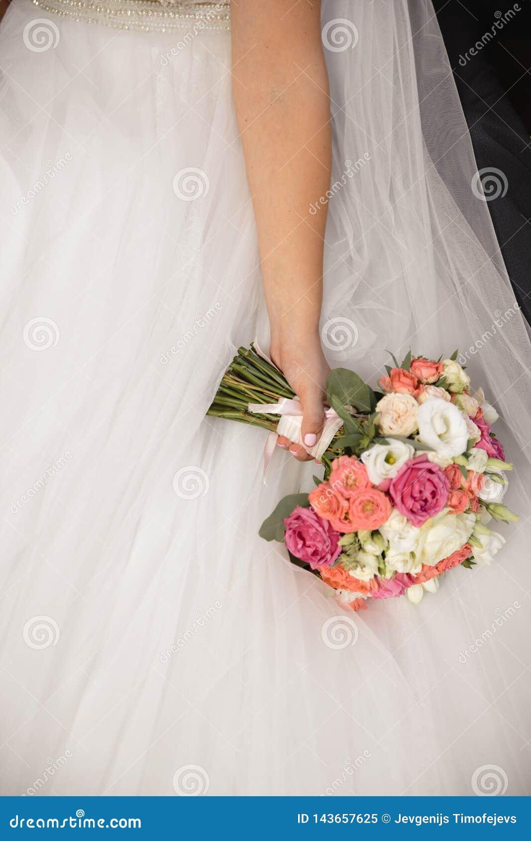 Casandose el ramo de las flores en la mano de la novia - novia en vestido de boda