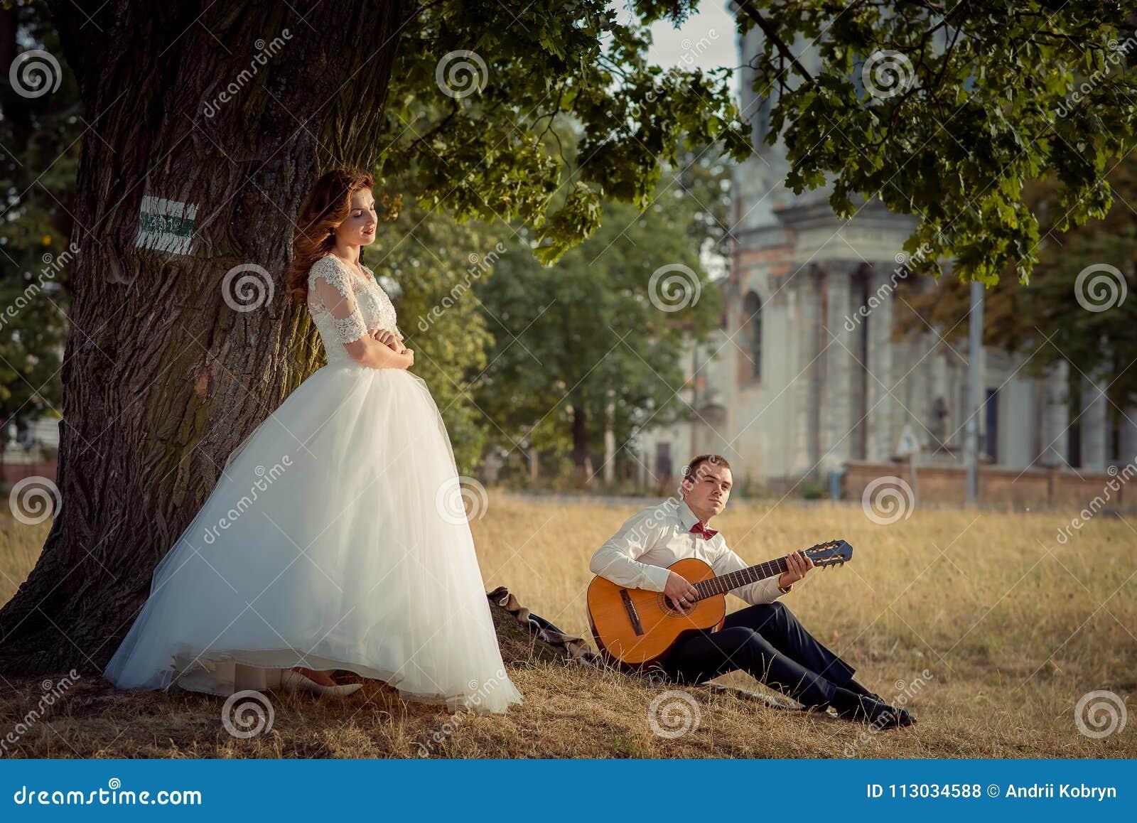 Casarse el retrato al aire libre El novio hermoso está tocando la guitarra mientras que su novia encantadora del pelo del jengibr