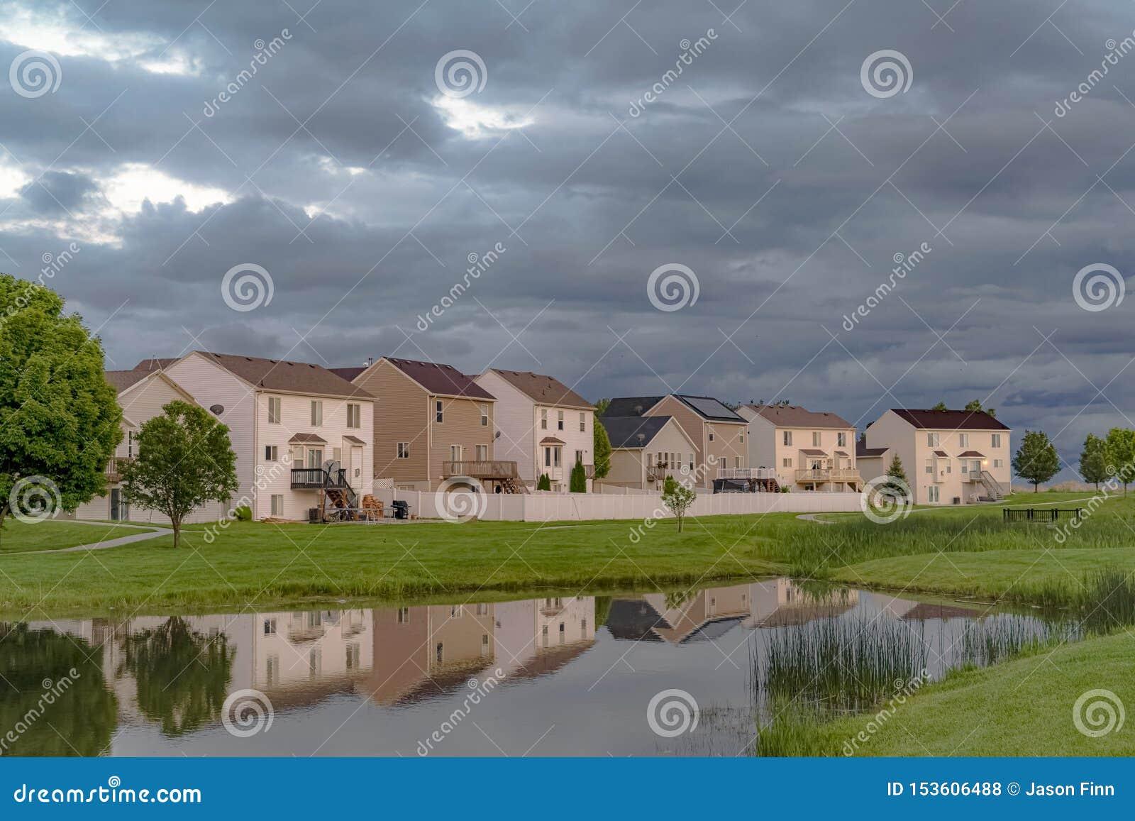 Casas bonitas com uma ideia cênico de uma lagoa brilhante e de um caro campo gramíneo
