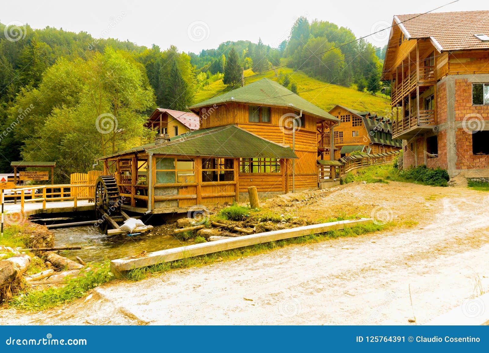 Casas de campo do feriado nas montanhas ao lado de um moinho de água