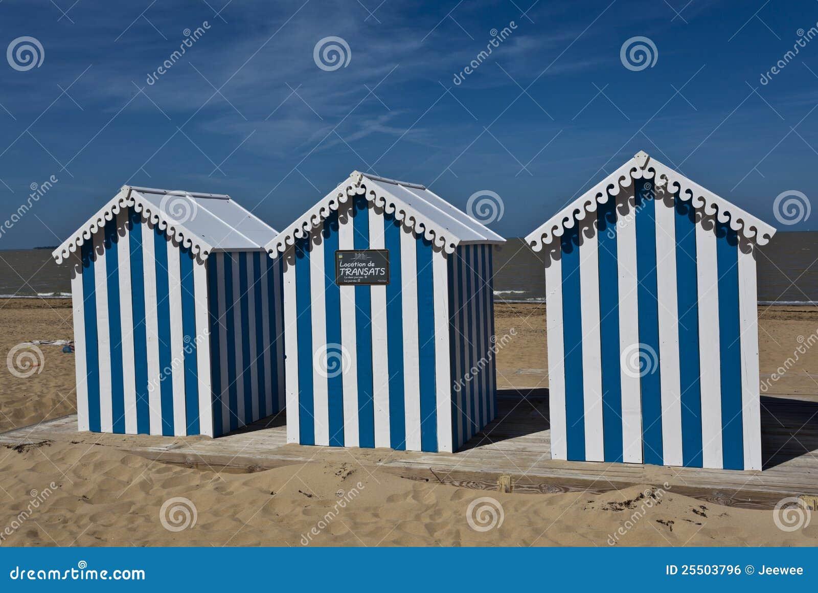 Casas de playa rayadas blancas y azules en una playa asoleada