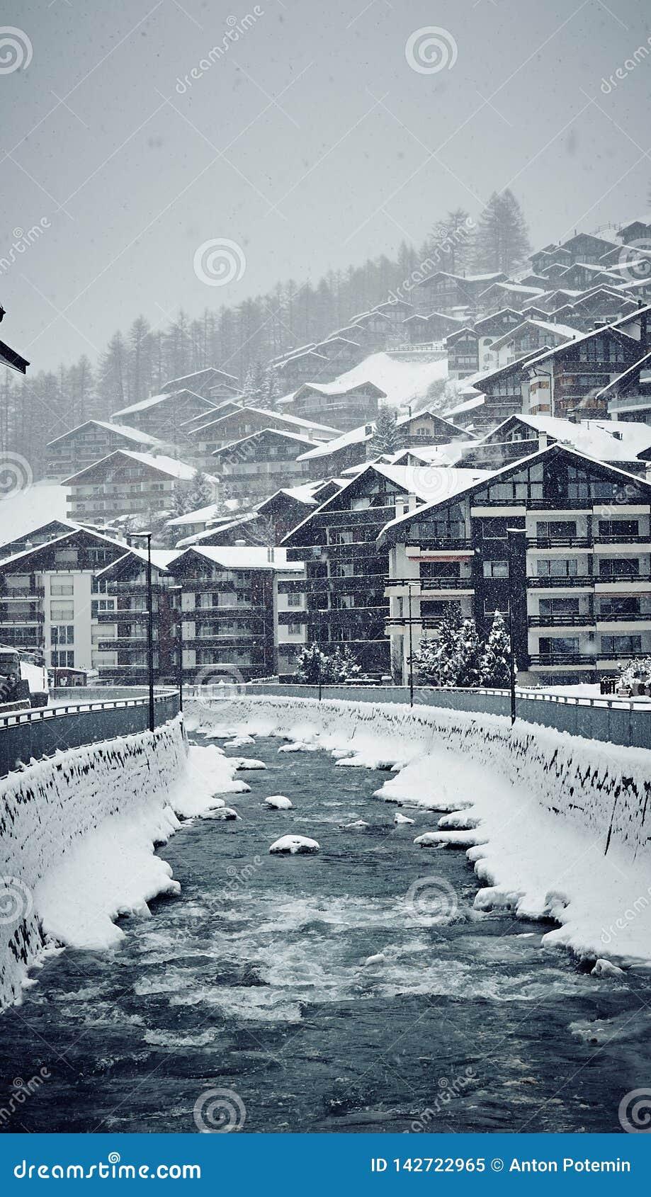 Casas de Zermatt do inverno e o rio