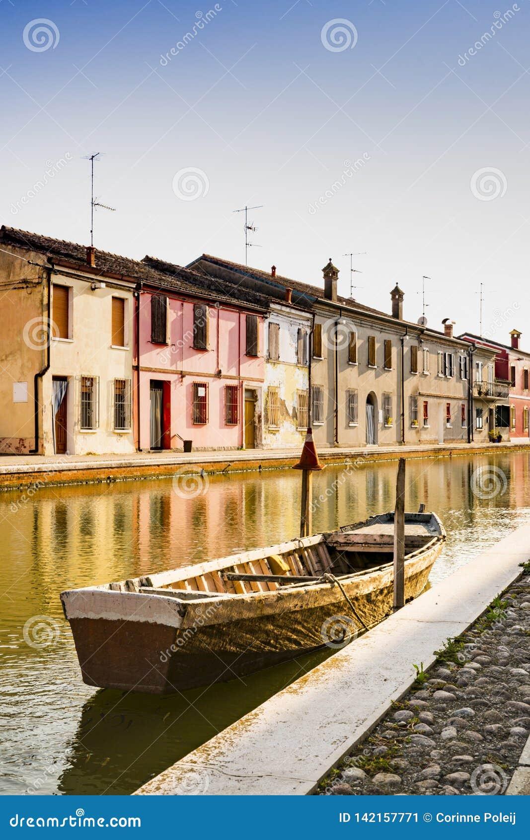Casas e barco no canal de Comacchio, Itália