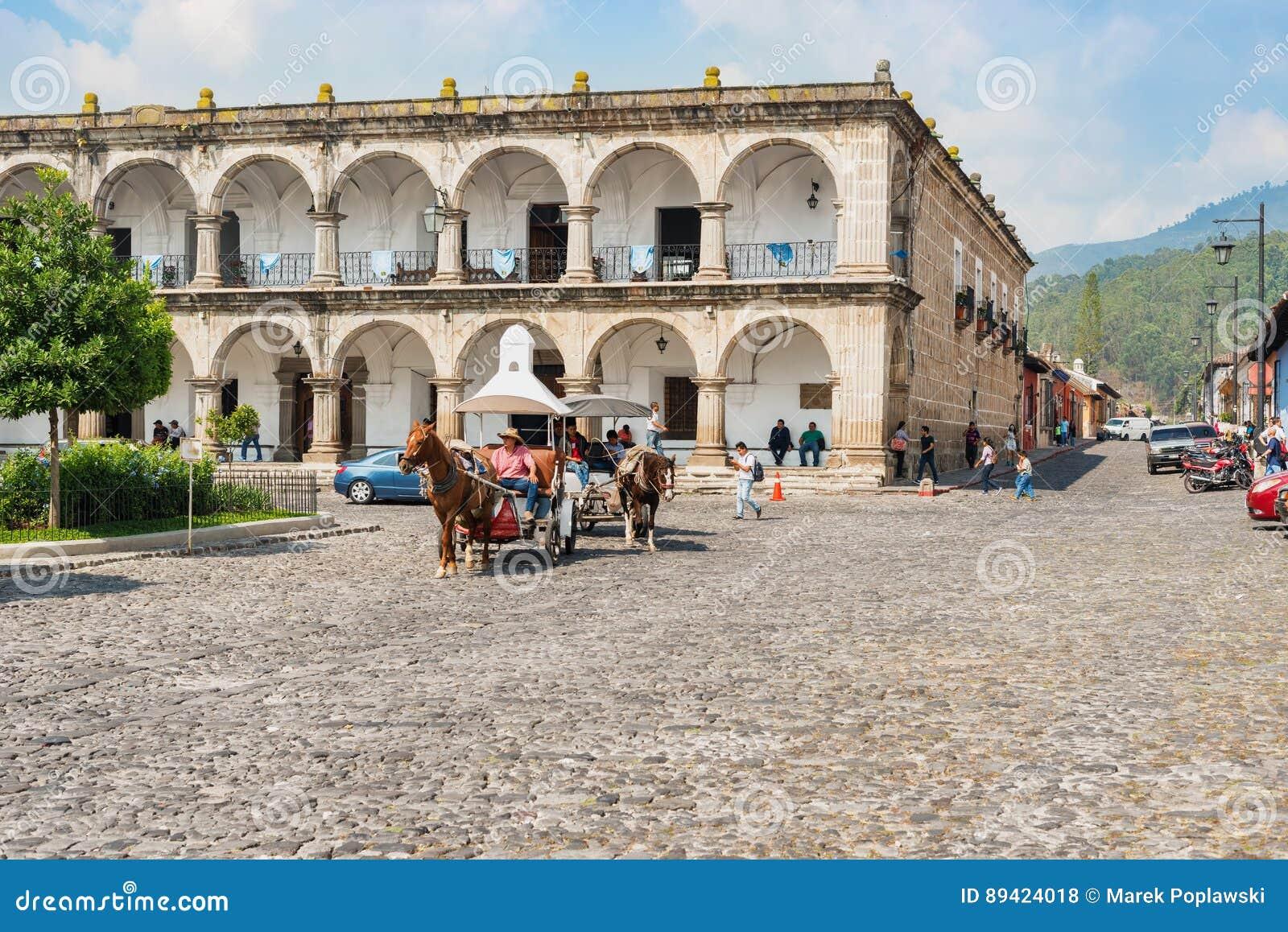 Casas e tráfego pela plaza principal em Antígua, Guatemala