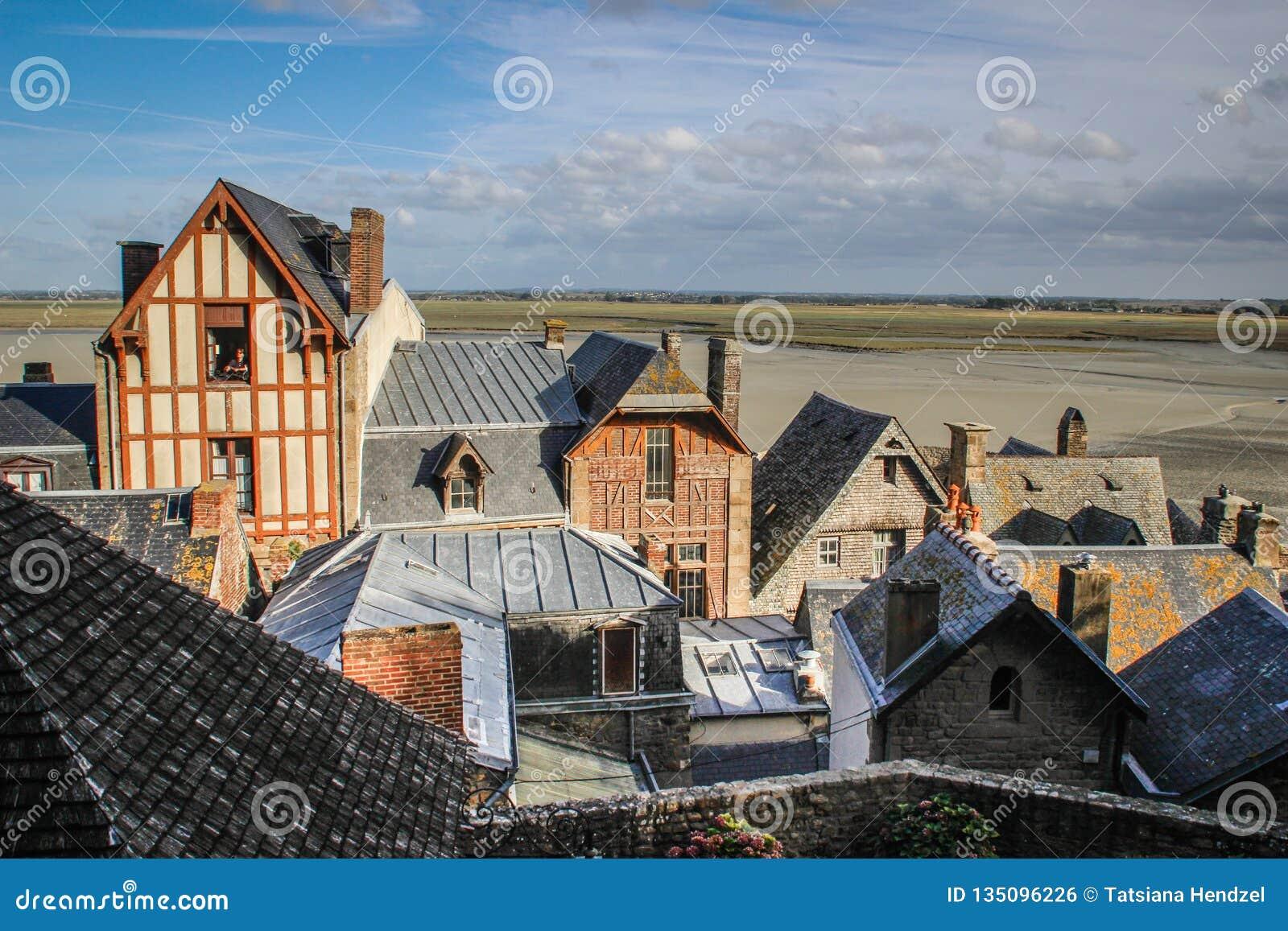 Casas medievales de piedra con los modelos en las paredes y los tejados en la ciudad de la abadía del Saint Michel