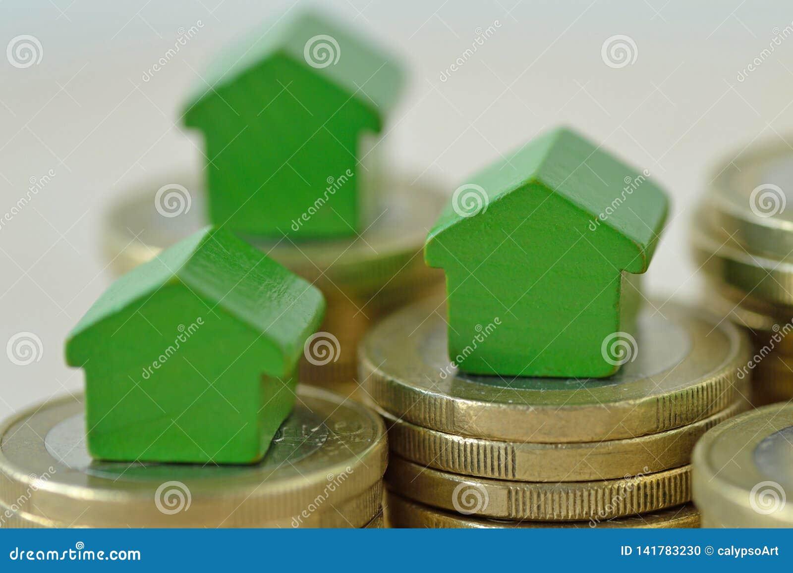 Casas miniatura verdes en las pilas de la moneda - concepto de inversión inmobiliaria, de hipoteca, de seguro casero y de préstam