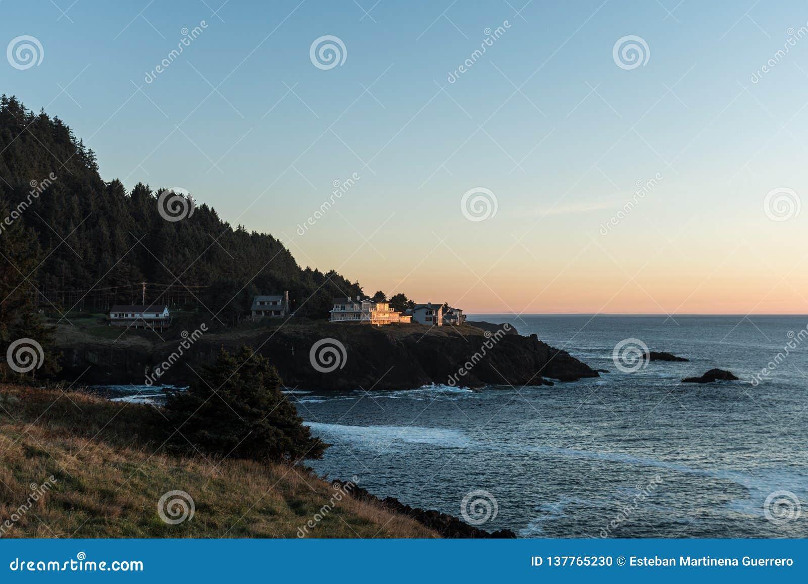 Casas na borda de um penhasco no por do sol em uma angra do Oceano Pacífico na costa de Oregon, EUA