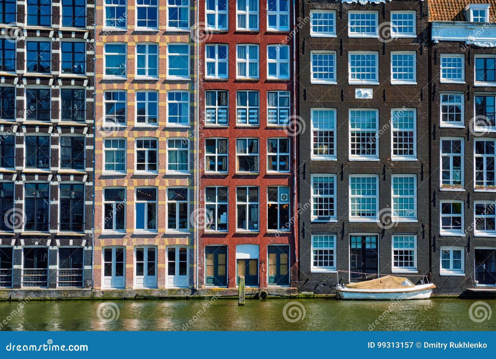 Casas y barco en el canal Damrak de Amsterdam con la reflexión ams