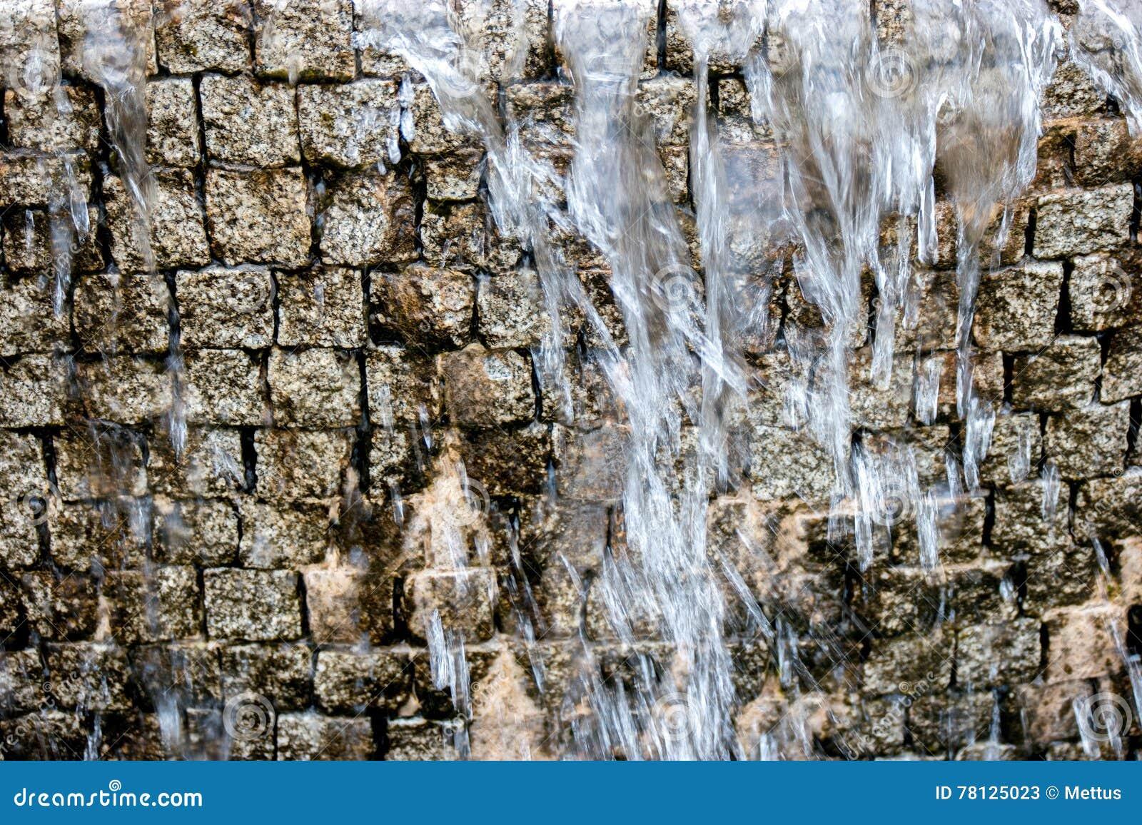 cascada artificial la corriente del agua cae abajo delante de la imitacin antigua de la pared de ladrillo