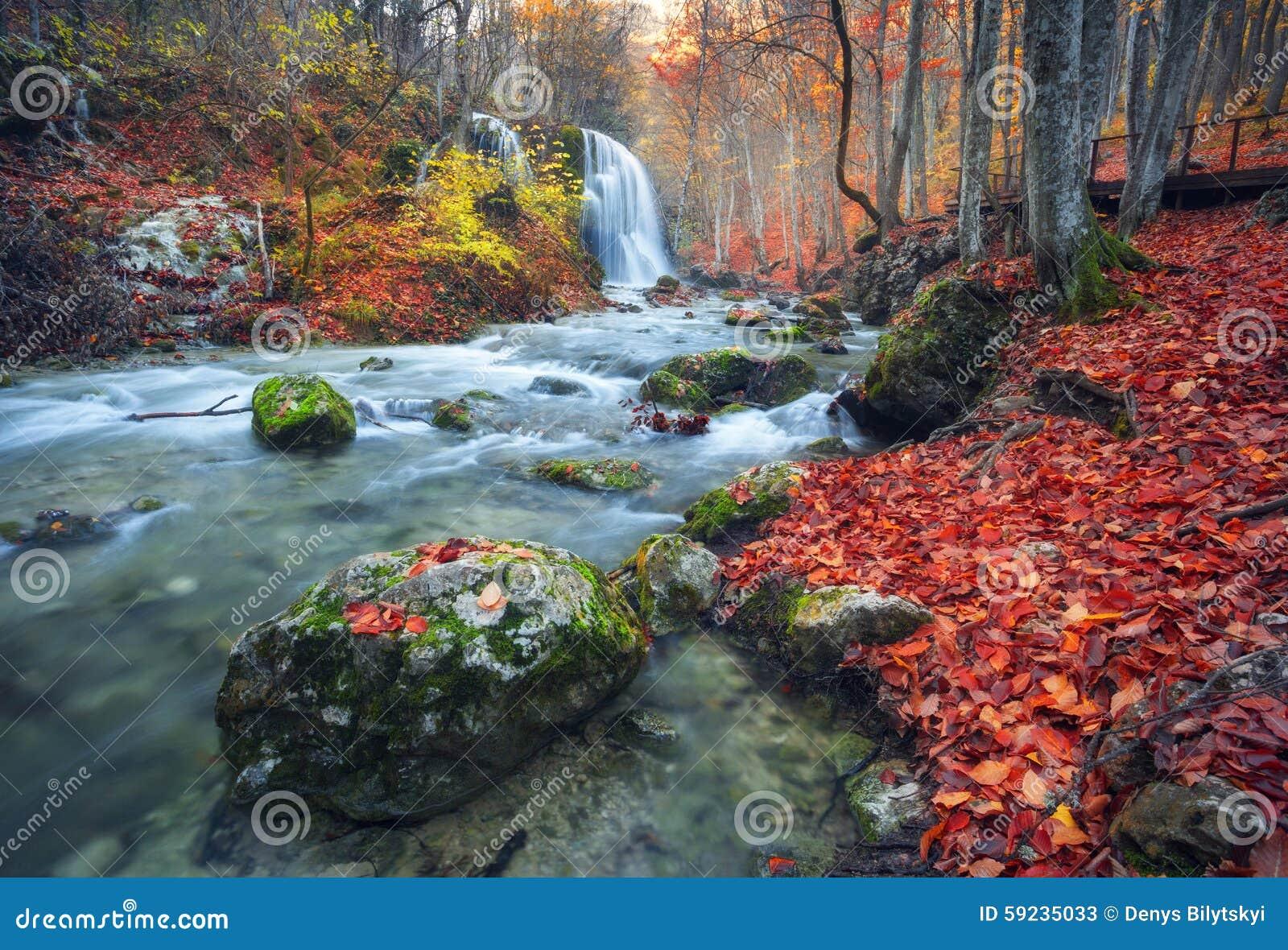Cascada hermosa en bosque del otoño en montañas crimeas en el sol