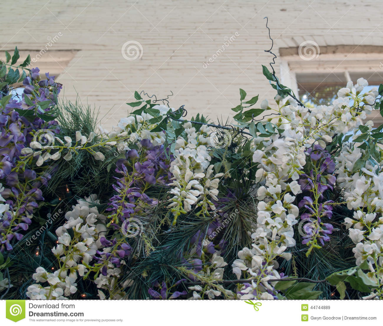 Cascading flowers in front of older brick building stock image royalty free stock photo mightylinksfo