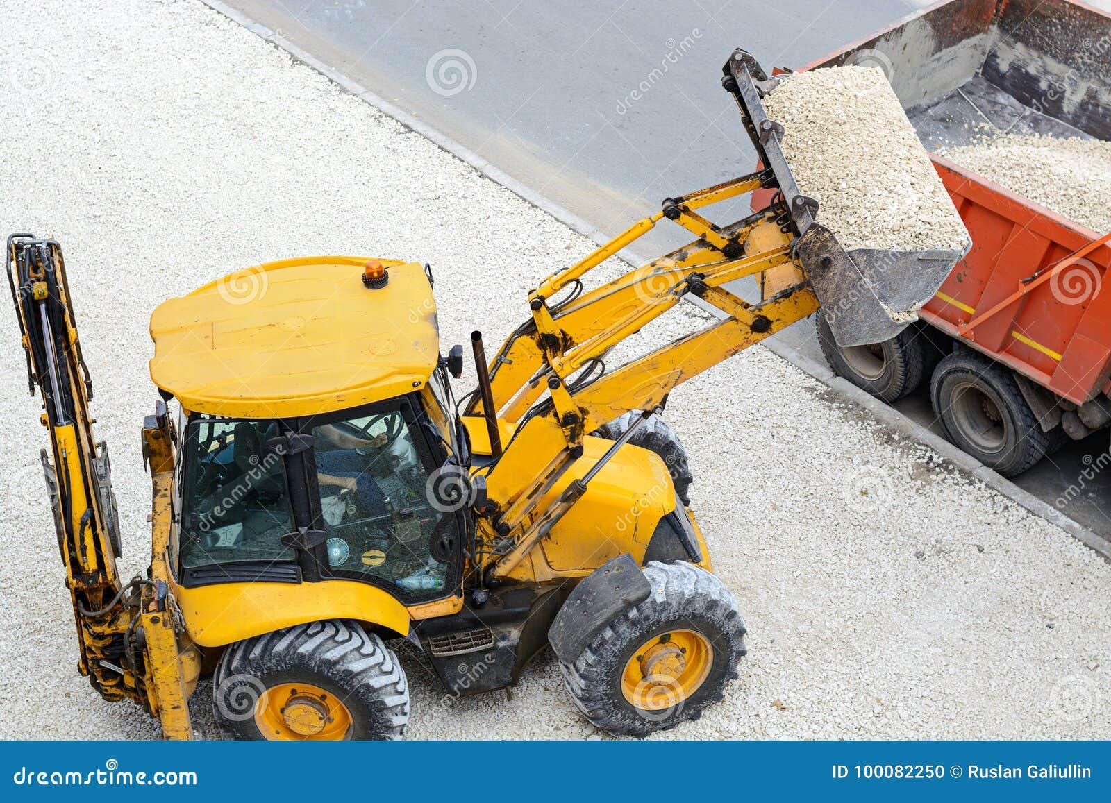 Cascalho da carga do trator em um caminhão Trabalhos de estrada