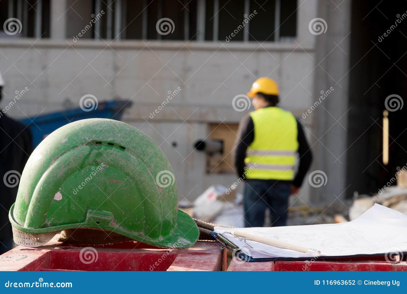 Casco de protección verde de la seguridad en primero plano Trabajador de construcción en fondo