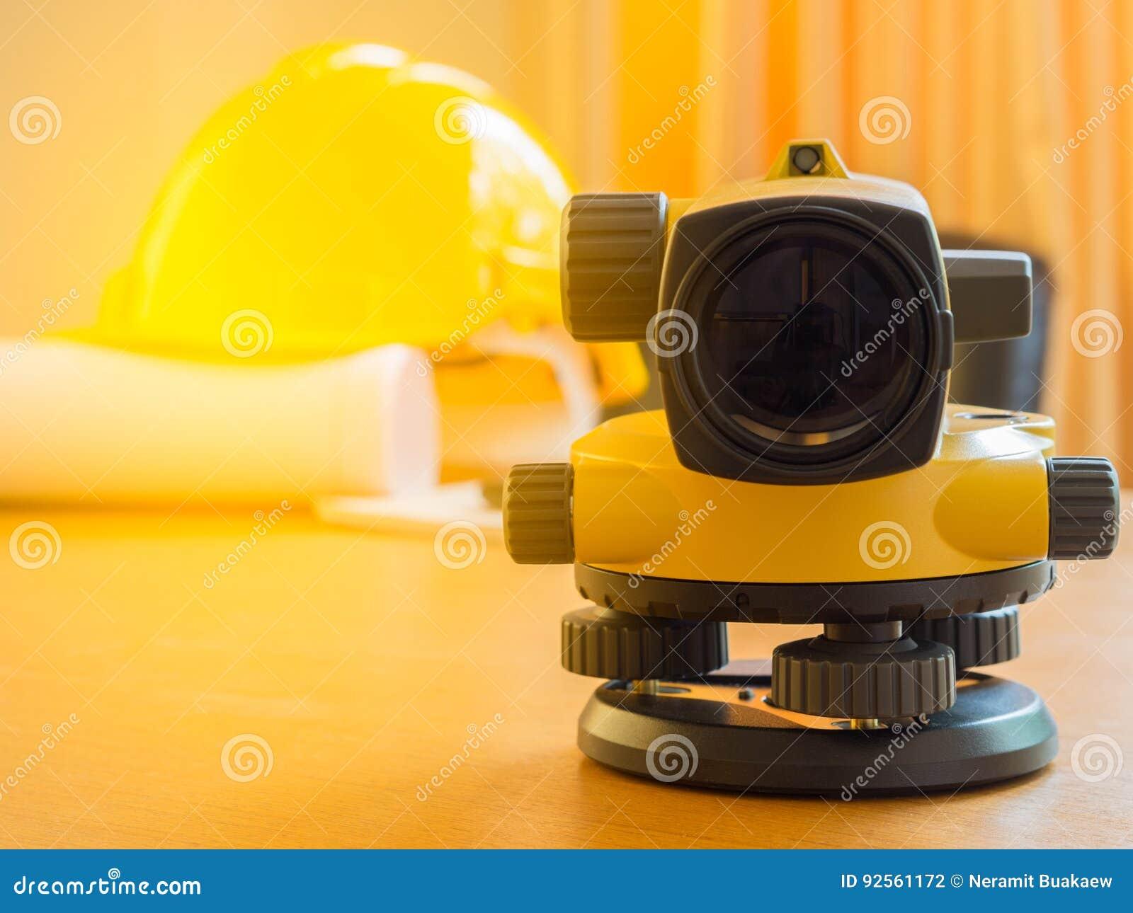 Casco della costruzione e del teodolite, rotoli e piani Sullo scrittorio Concetto di industria dell edilizia