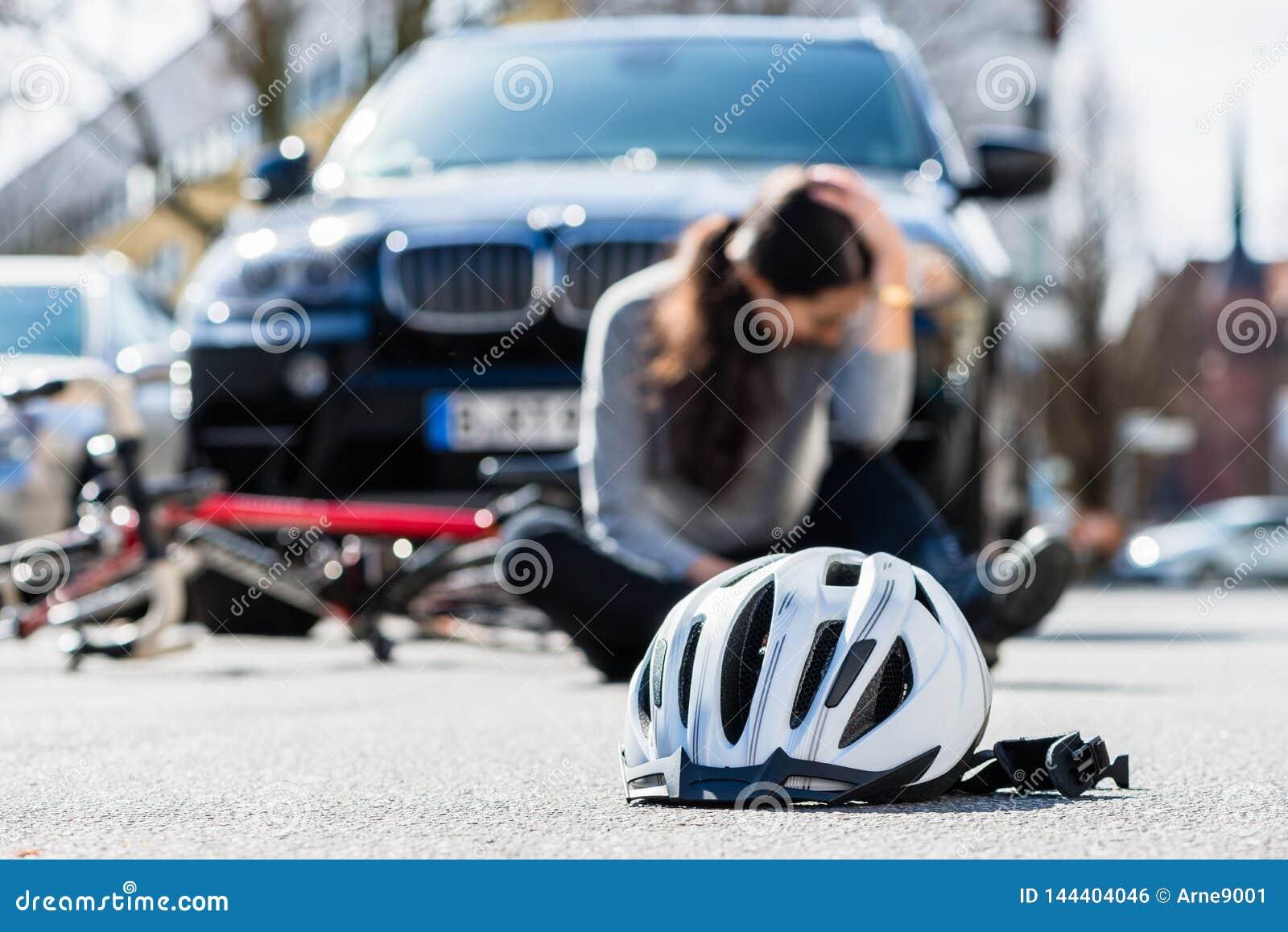 Casco sull asfalto dopo la collisione accidentale fra la bicicletta e l automobile