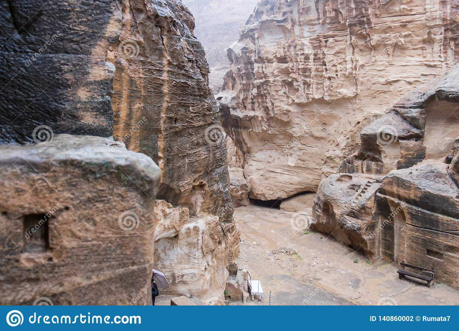 Case o tombe di pietra in rocce curve a pioggia persistente in poco PETRA - città antica di Nabatean