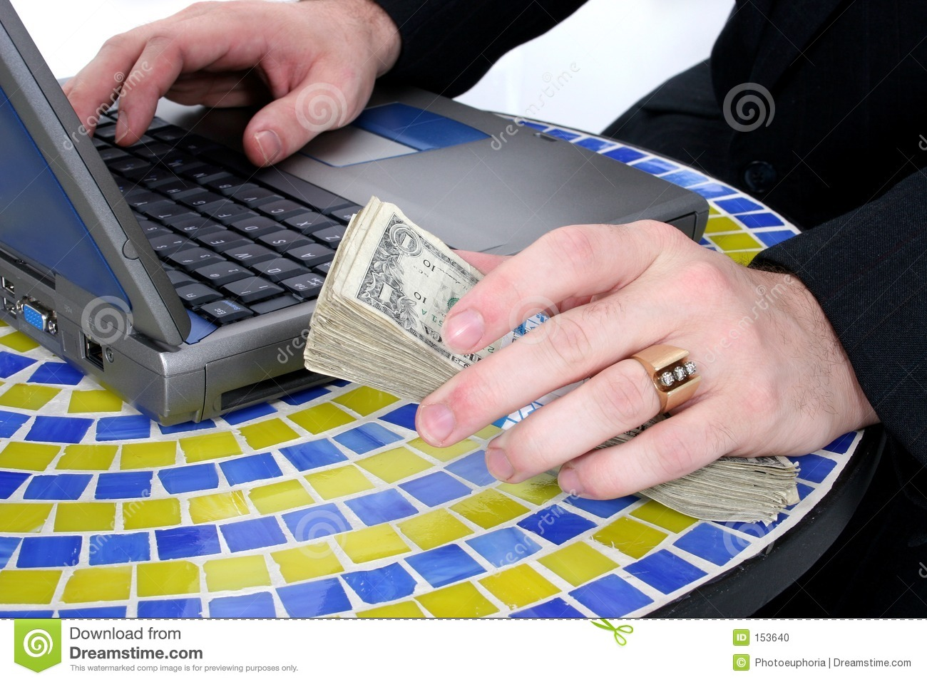 Cash In Hand Resting On Table Top Near Laptop
