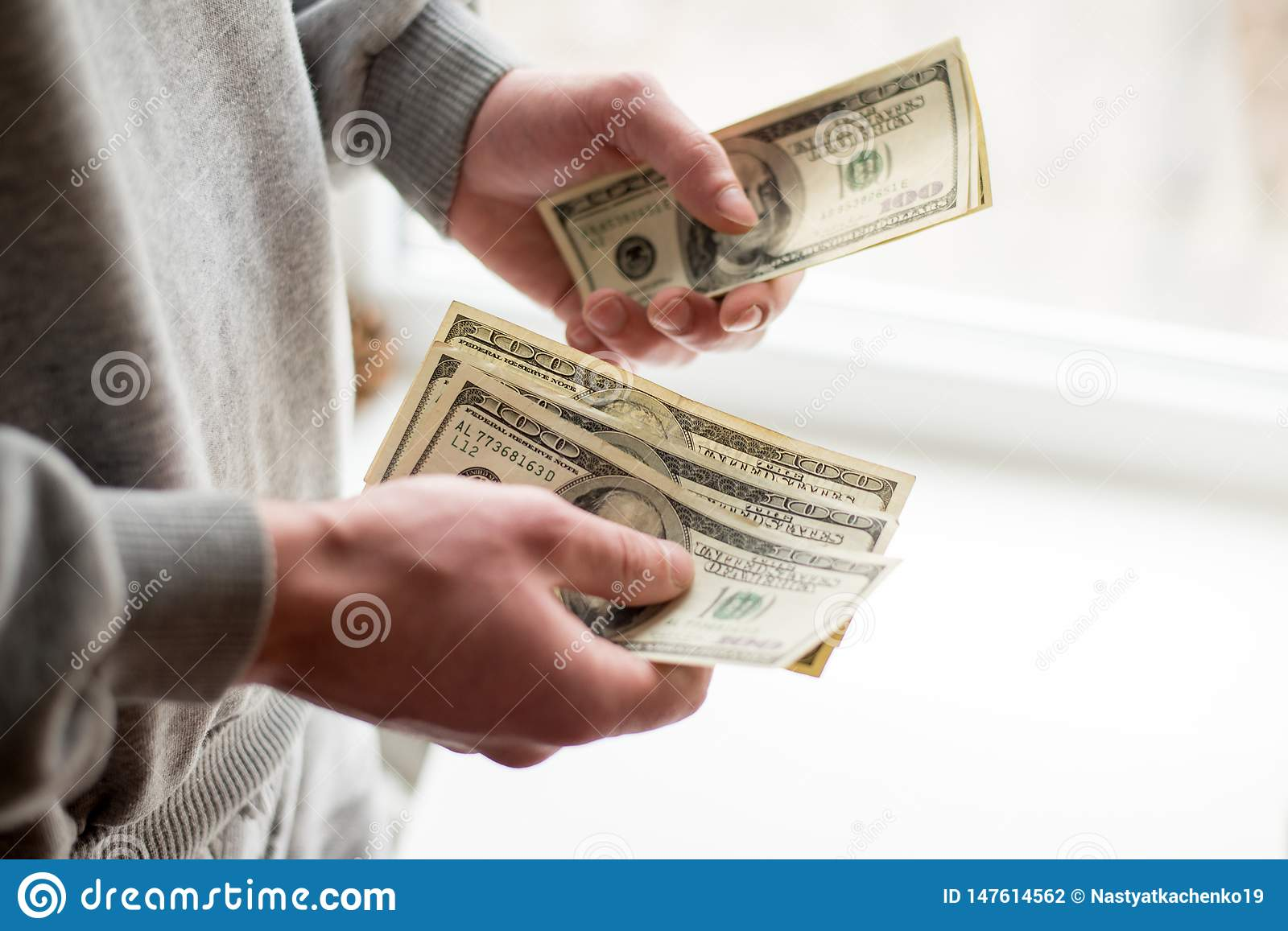 Cash in hands. Profits, savings. Stack of dollars. Man counting money. Dollars in man`s hands. Success, motivation, financial