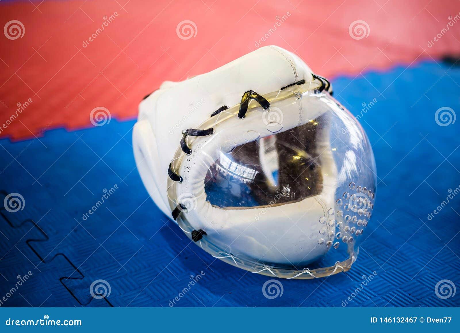Casques de protection blancs avec le masque plactic clair pour des arts martiaux sur le plancher bleu rouge